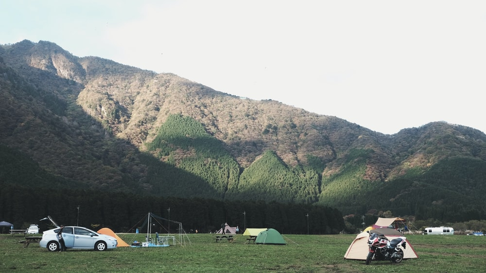 assorted-color dome tents near mountains under white clouds during daytime