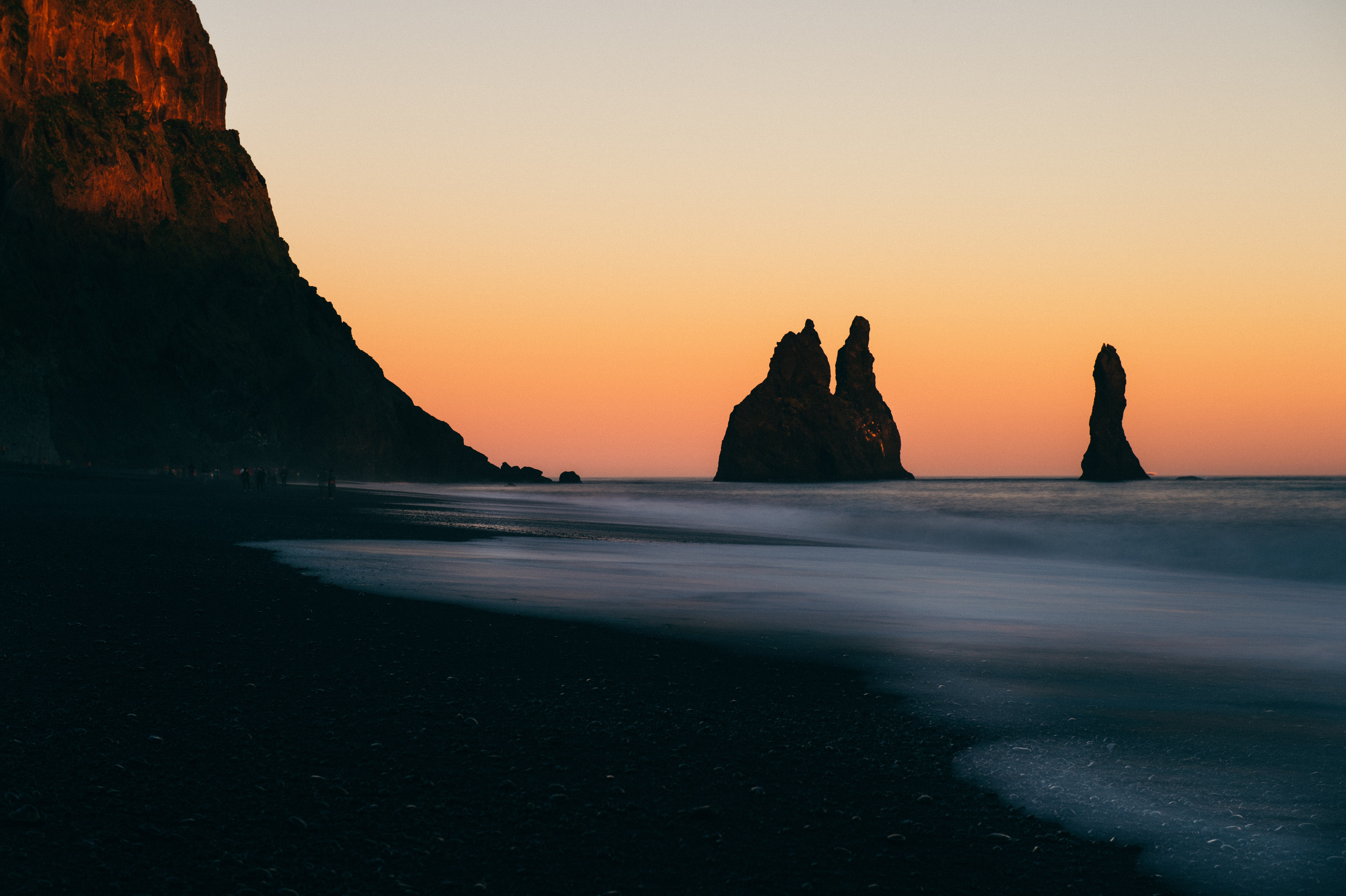 Silhouettes of rock formations in the ocean in Vik