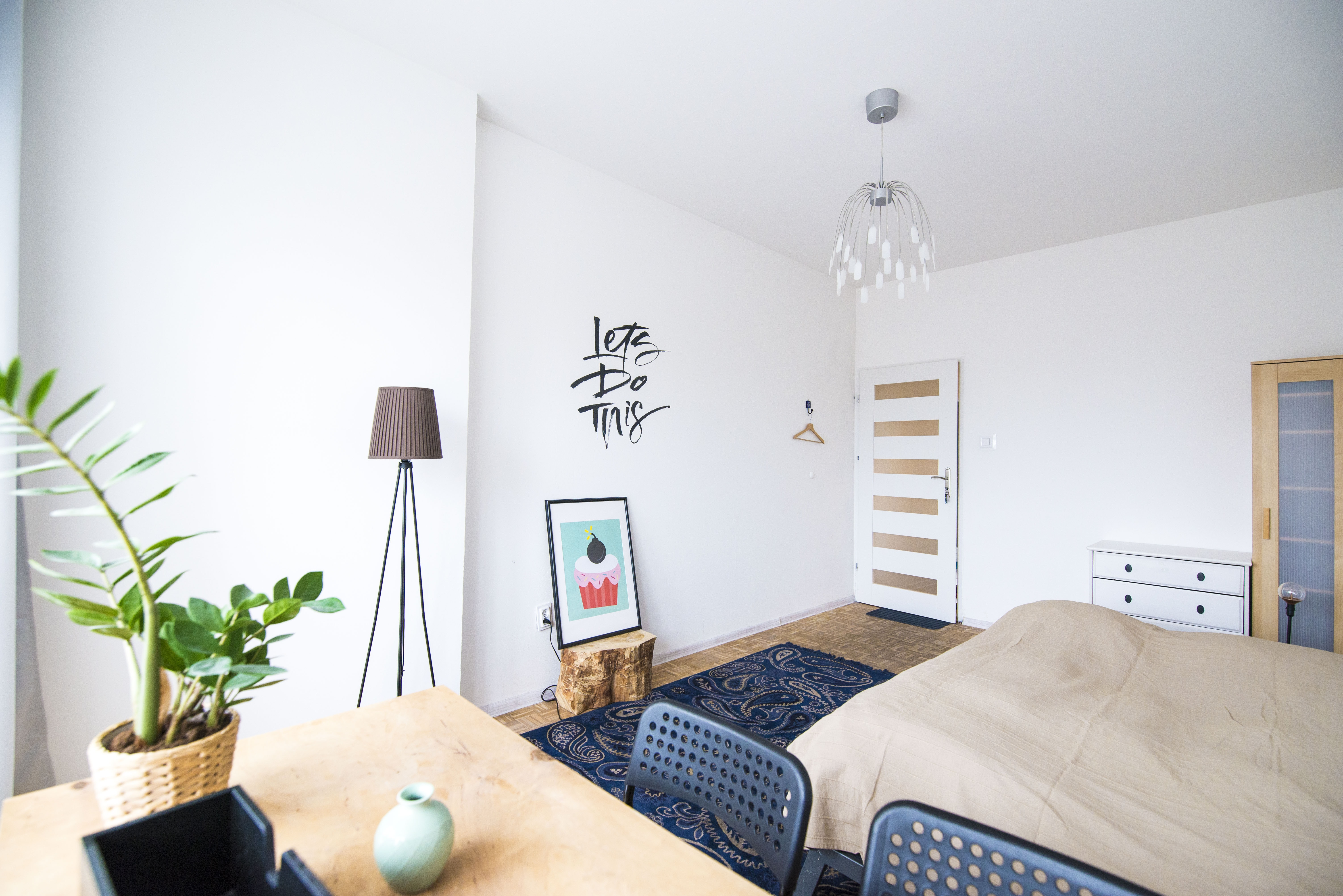 A bedroom with a lamp, sofa, bed, desk, plant, painting, and light fixture