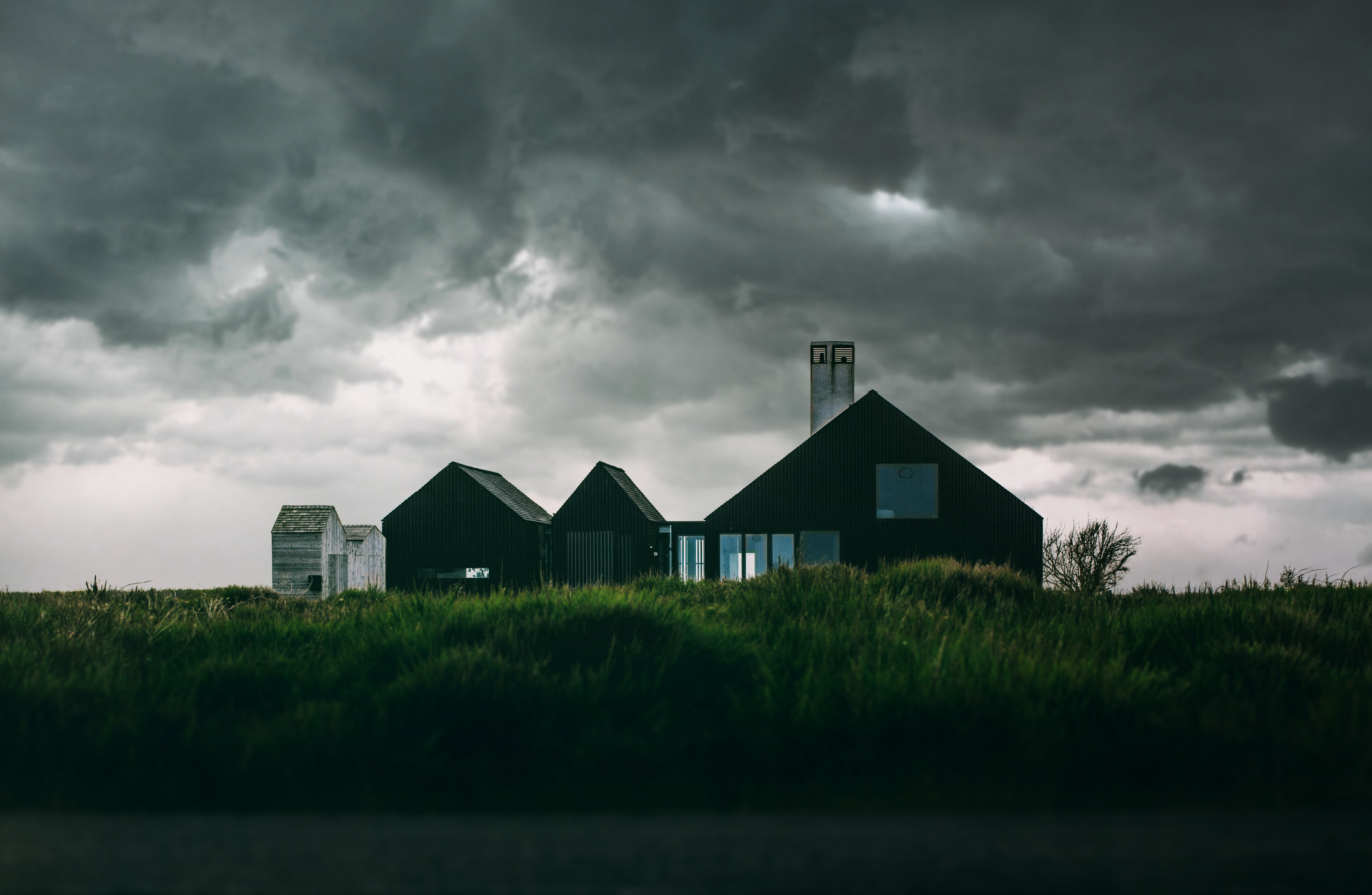 Single house in the middle of a green field with dark storm clouds gathering overhead