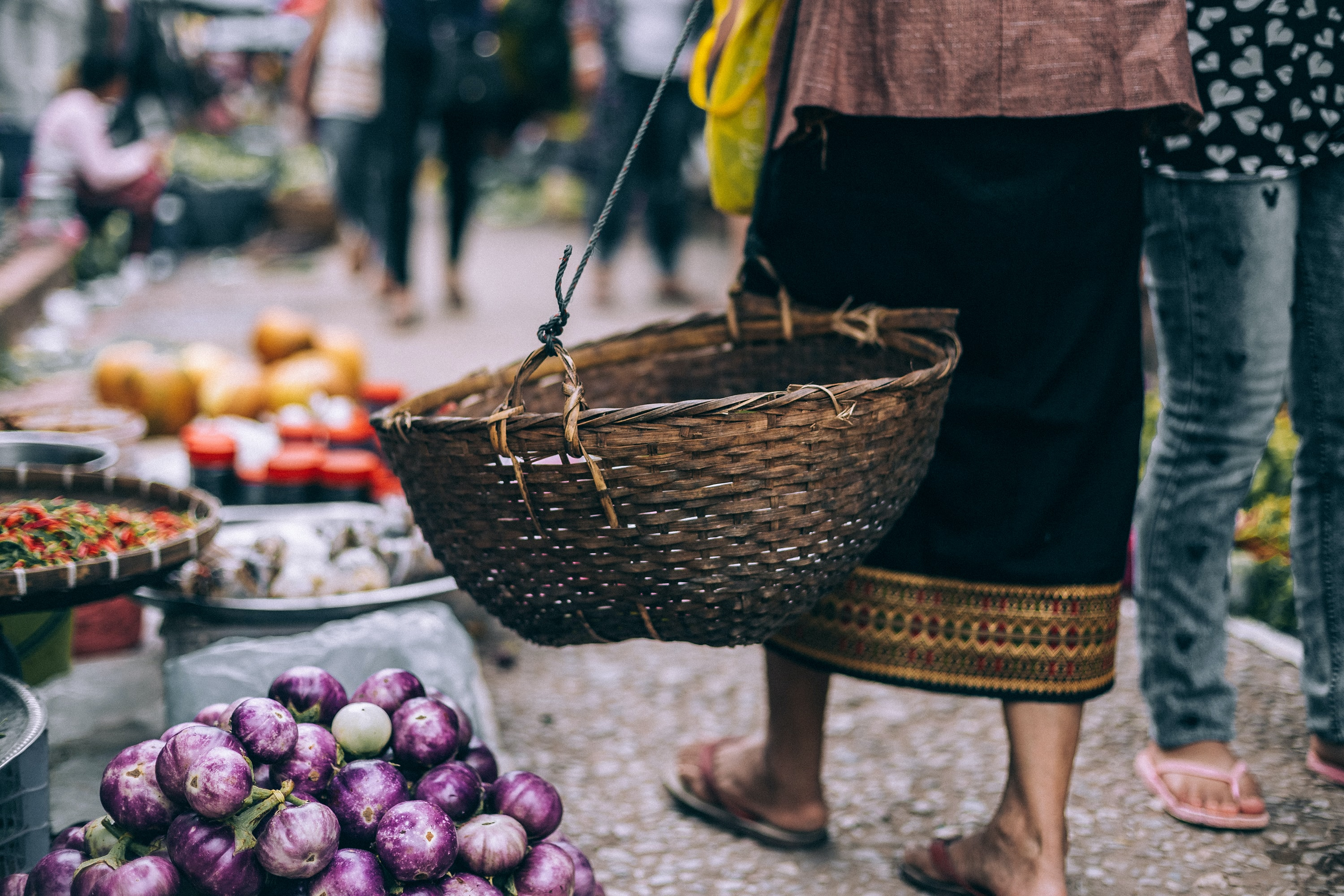 People walk through an Asian produce market with baskets