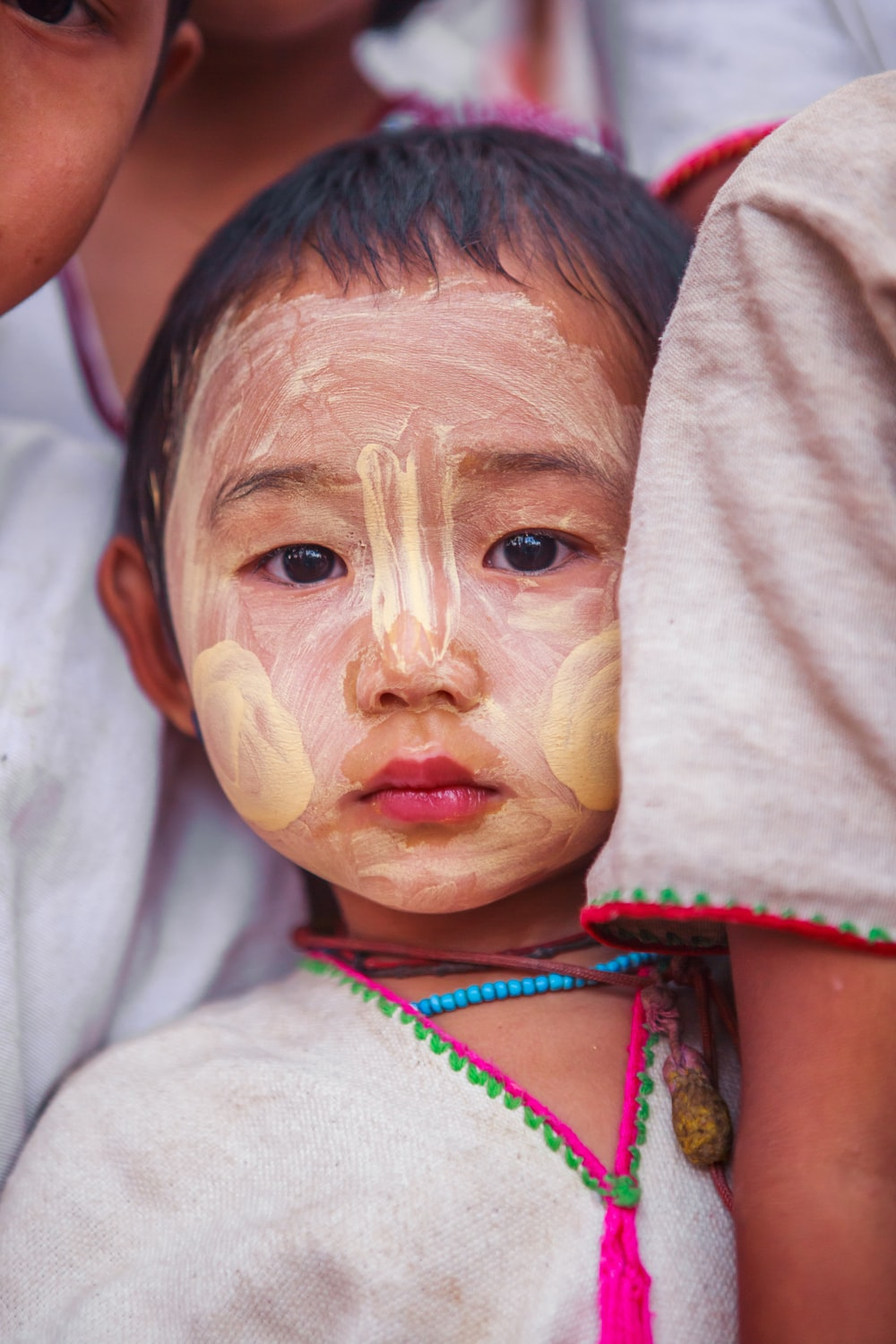 child with beige face paint