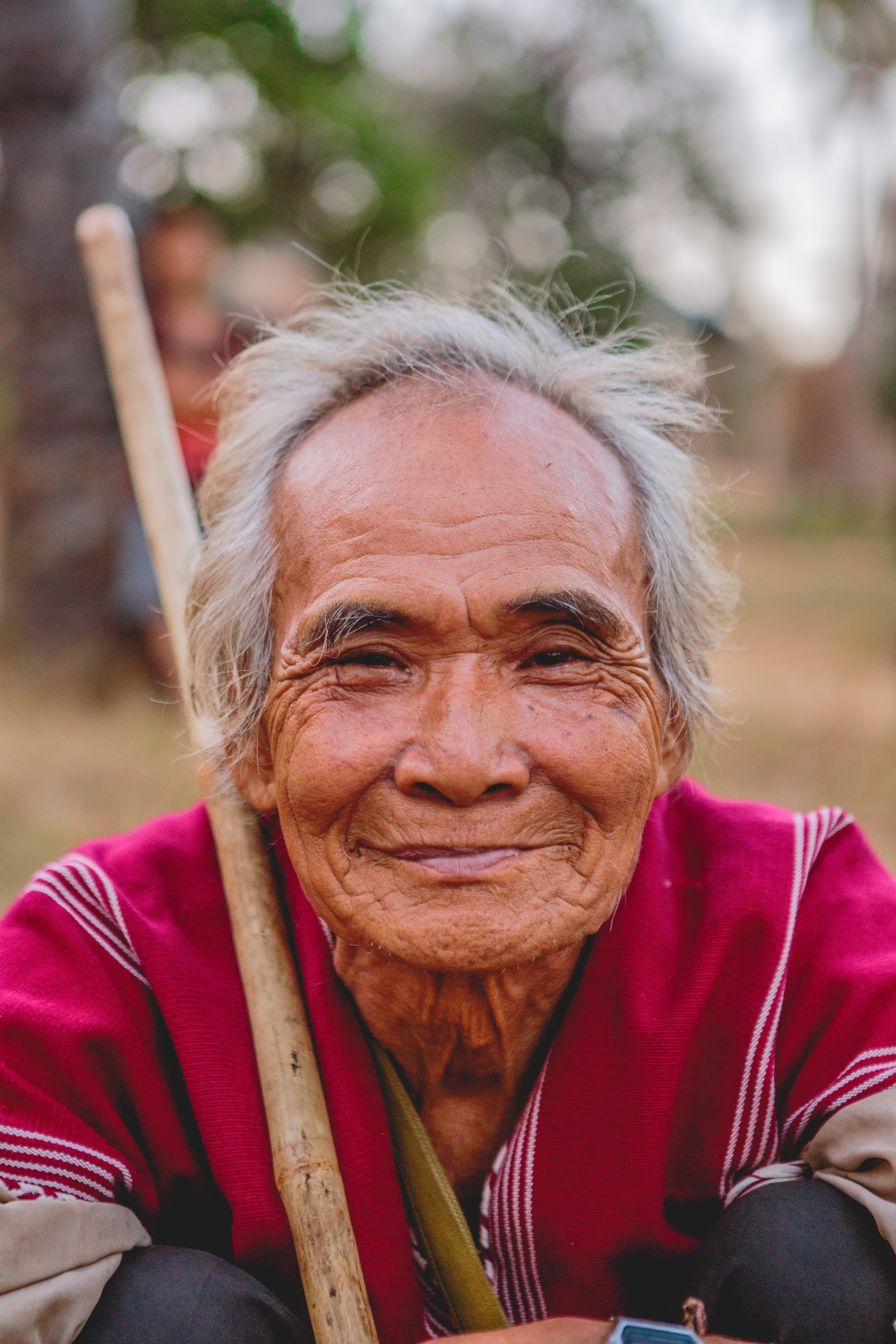 A portrait of a wrinkled elderly man smiling at the camera while holding a walking stick.