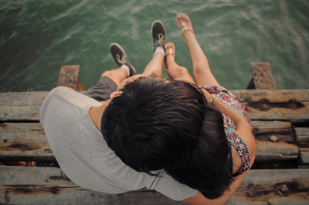 man and woman hugging each other on brown wooden dock
