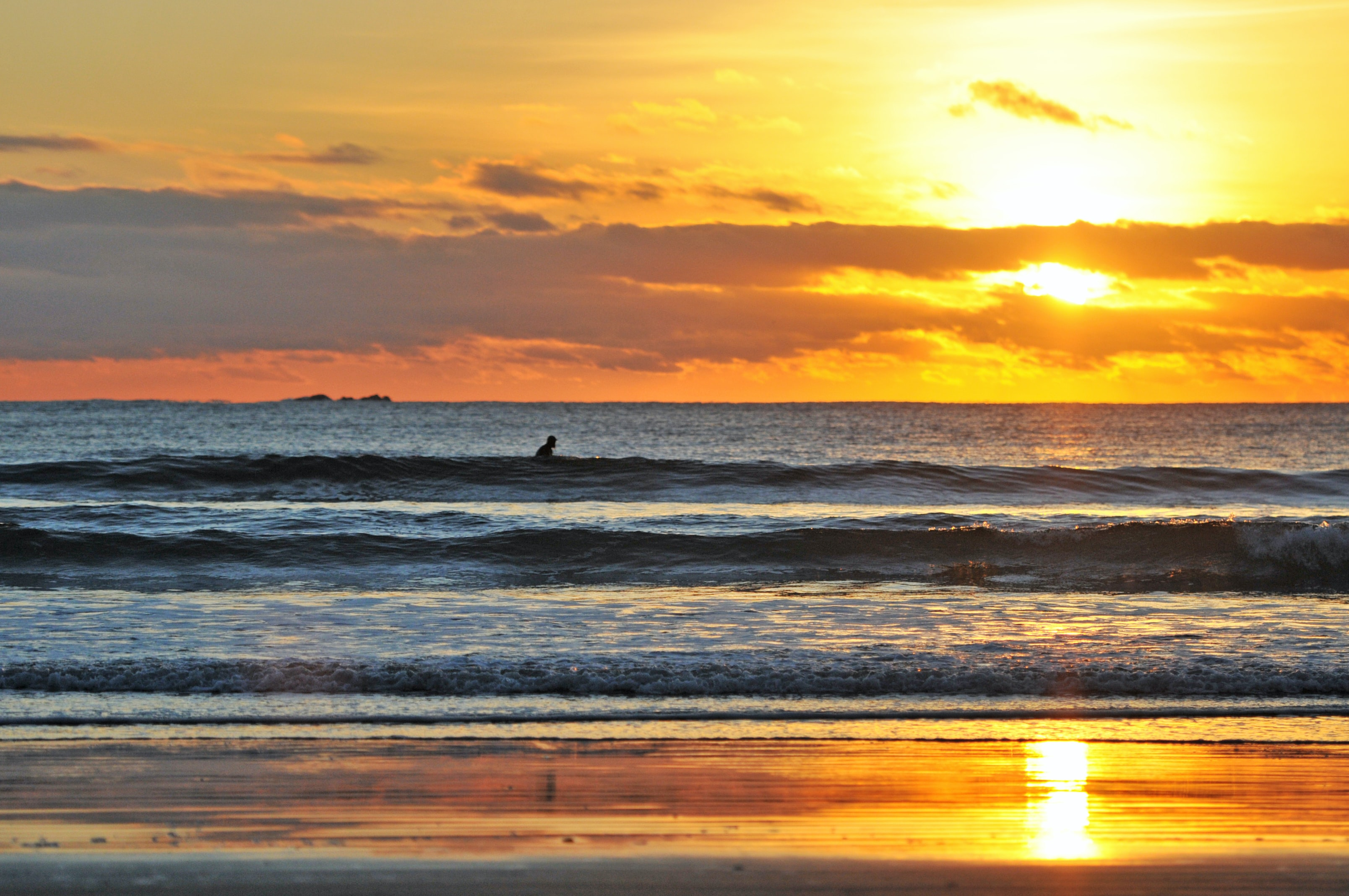 A view out to sea, rolling tide and one silhouette surfer waiting to catch the next wave as the sunrise-or-sunset lights the cloudy sky yellow and orange