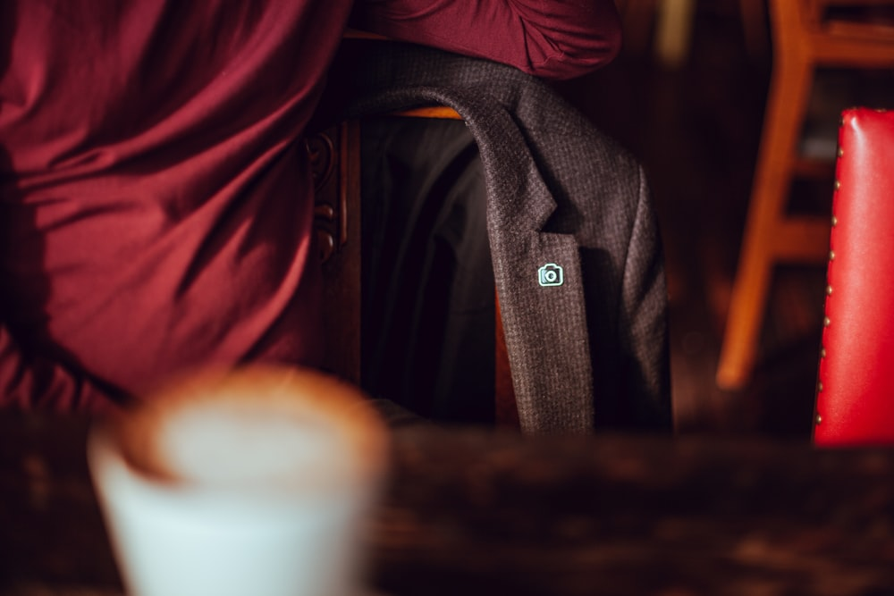 A blazer with an Unsplash pin, hanging on a chair at a cafe table