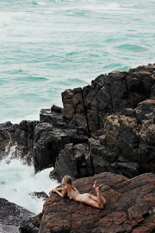 woman lying on rock formation on seashore