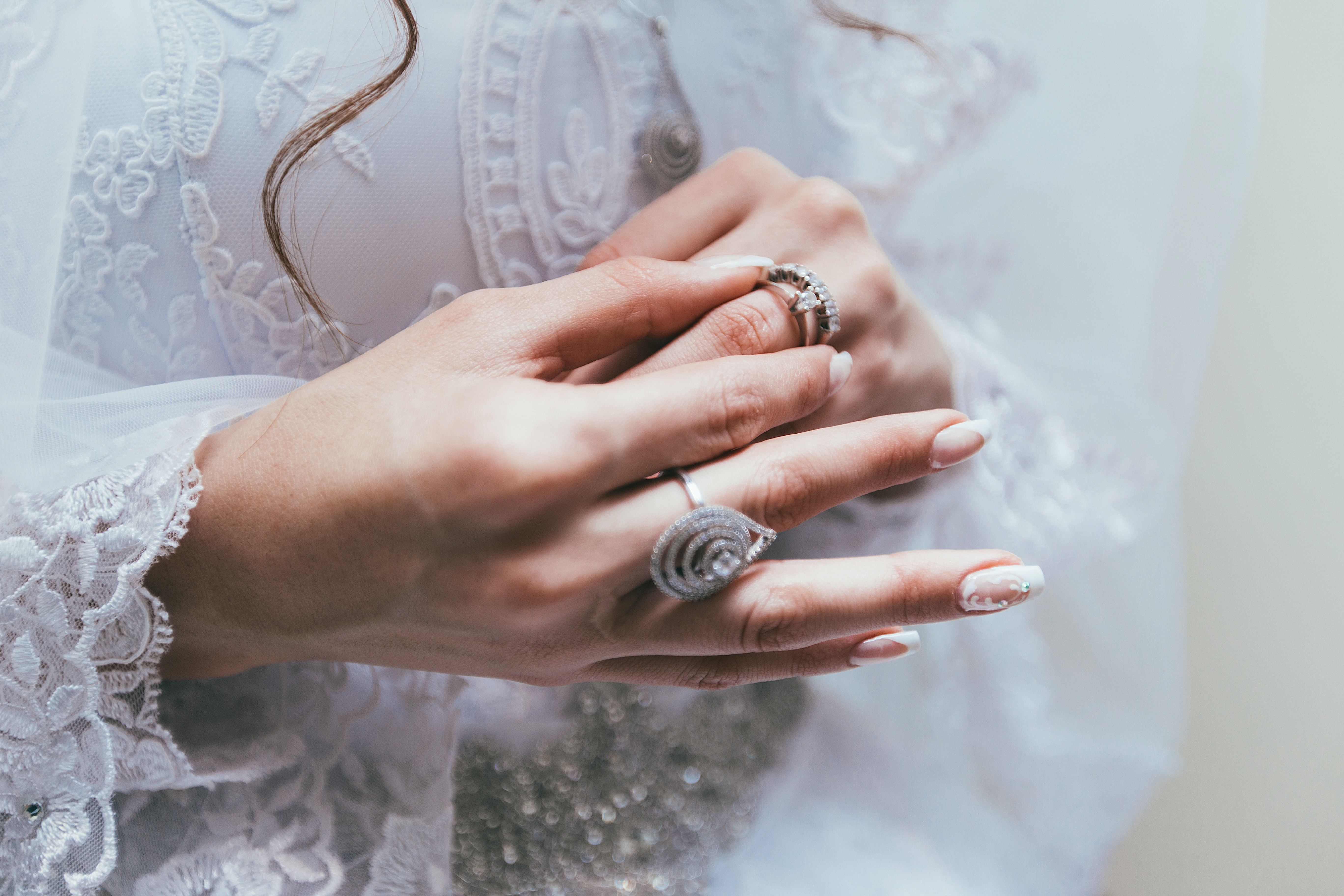 Texas bride touches her wedding ring on finger in front of white lace wedding dress