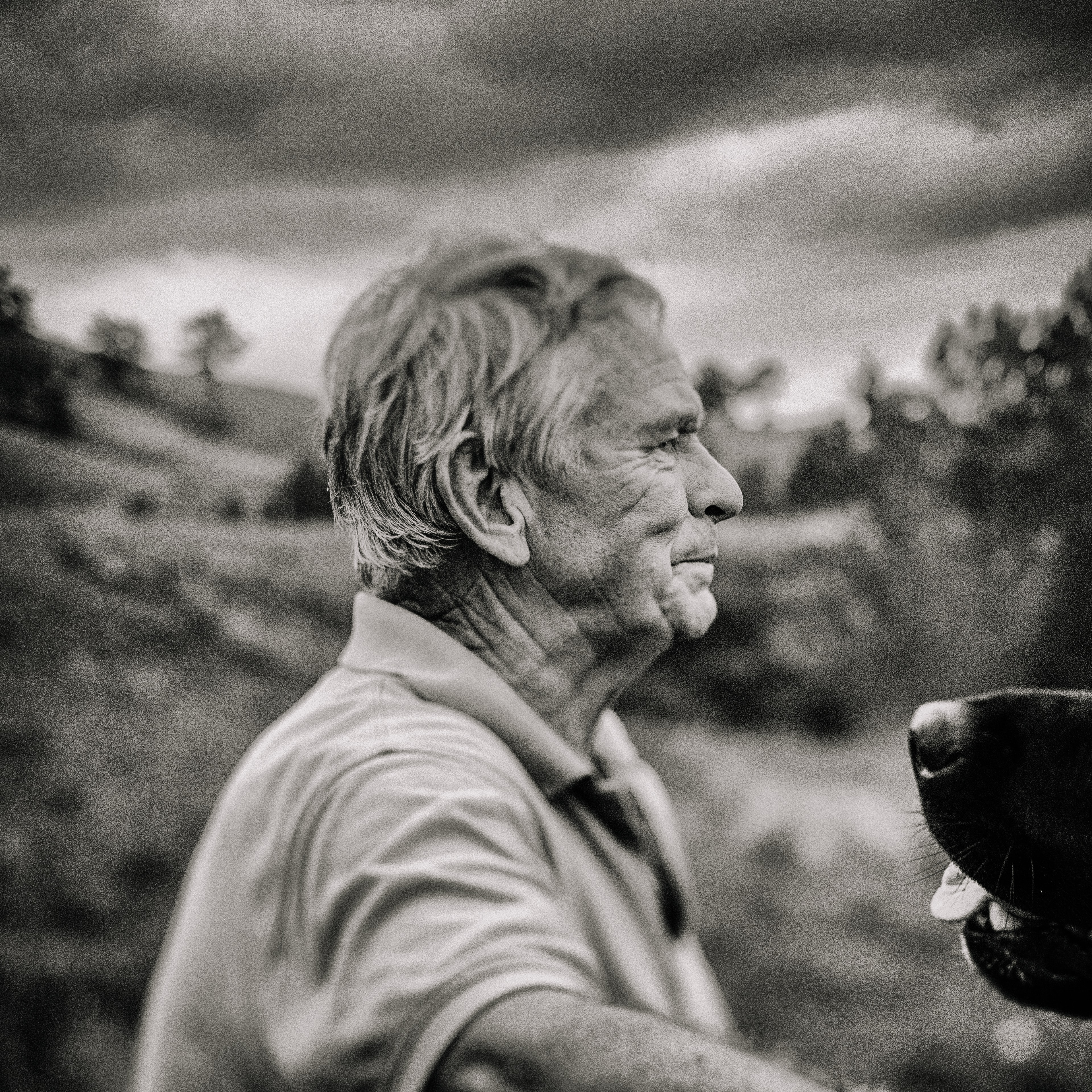 Old man looking out into the distance of a field in black and white.