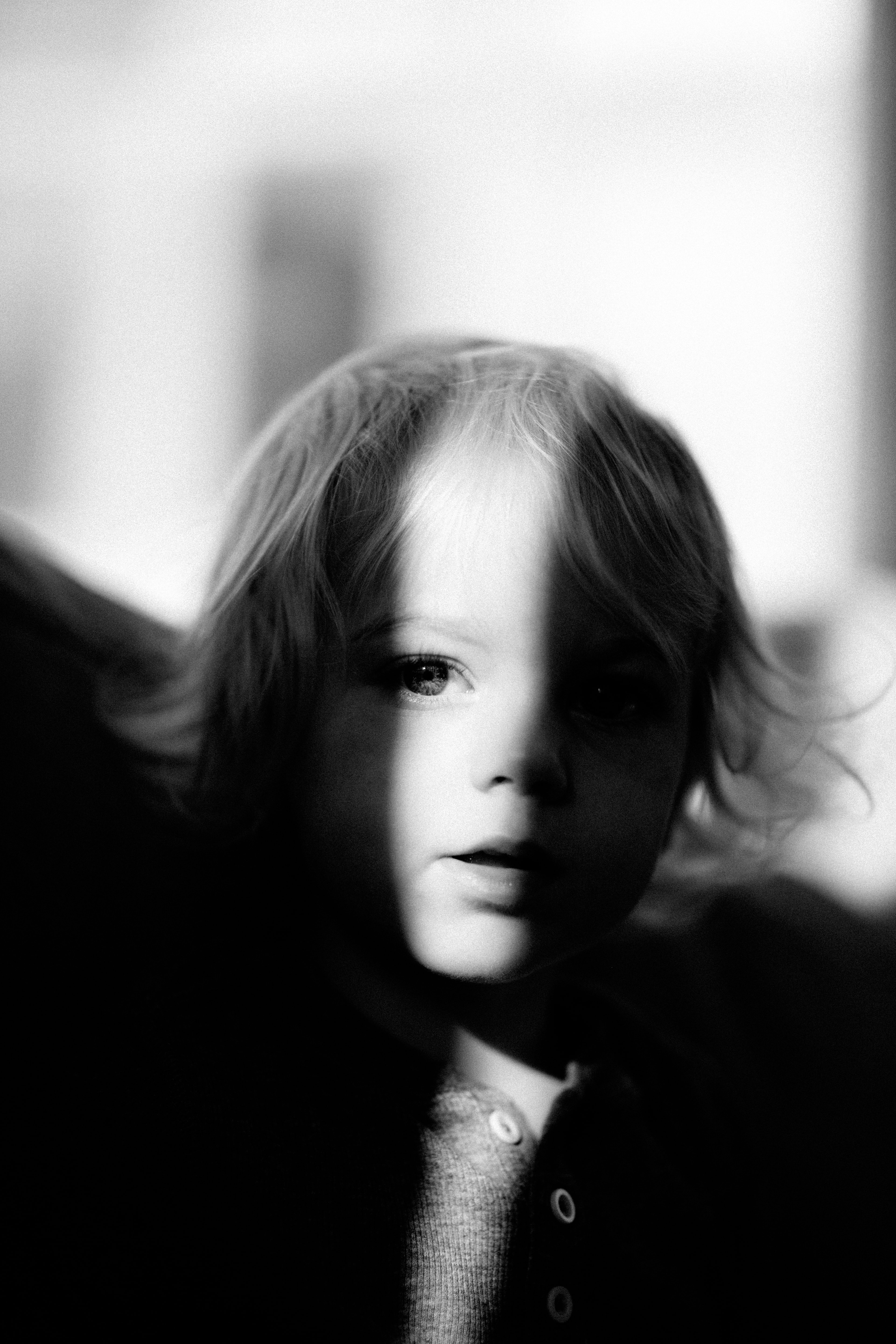 Black and white shot of young child with light and shadow on face, Castlecrag
