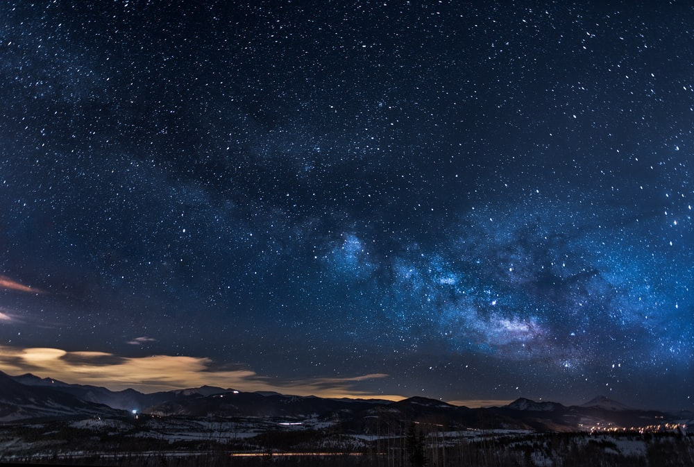 mountains with trees under white star at night