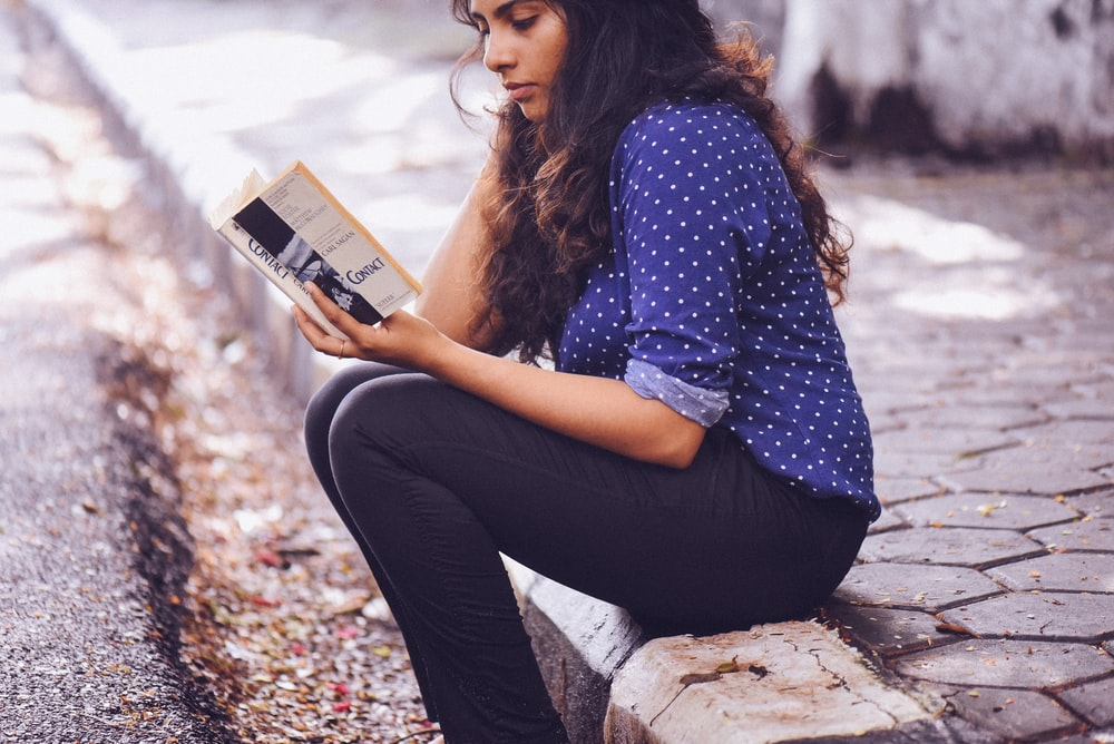 woman sitting on gutter reading book