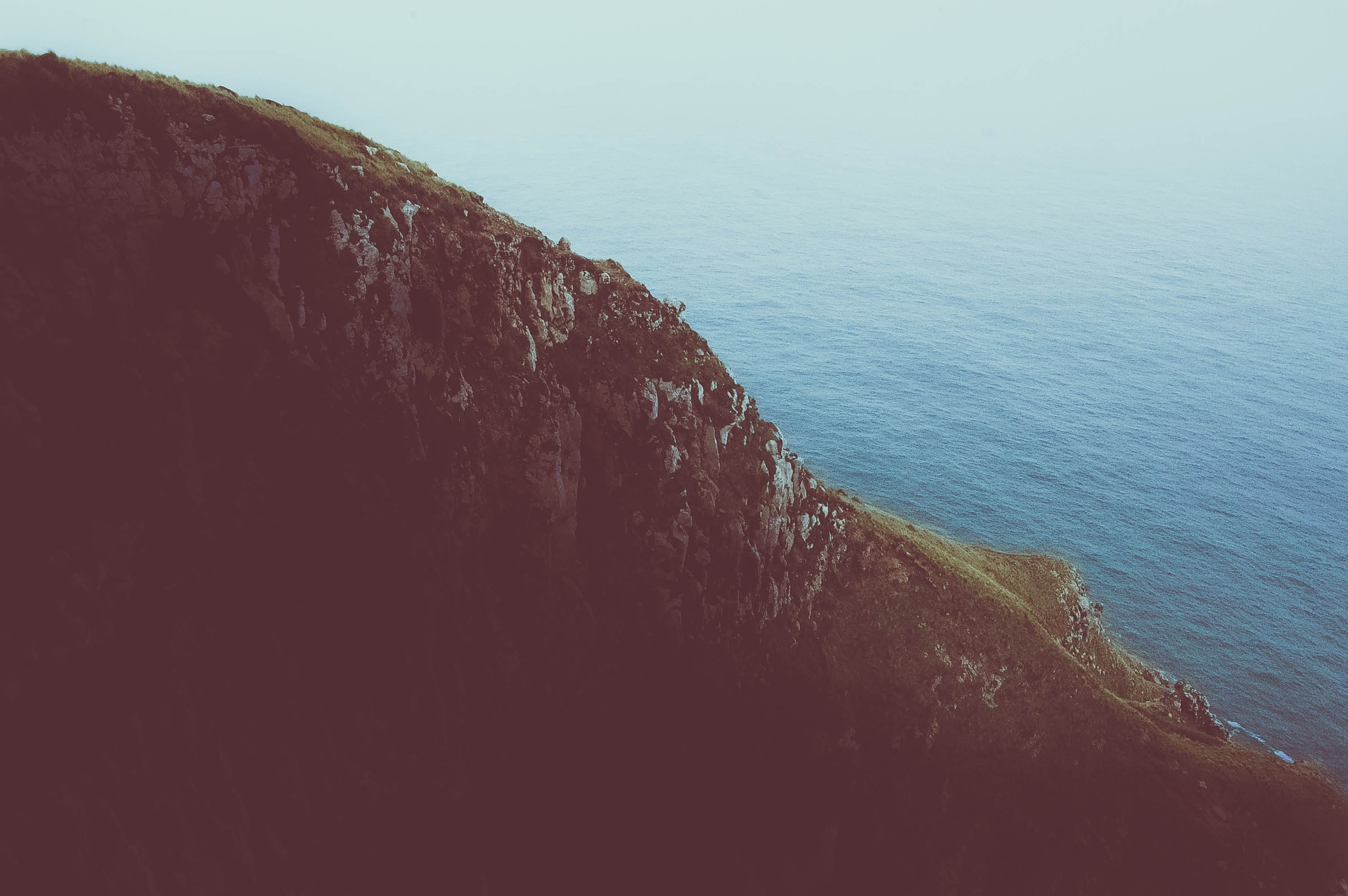 photo of cliff near calm sea during daytime