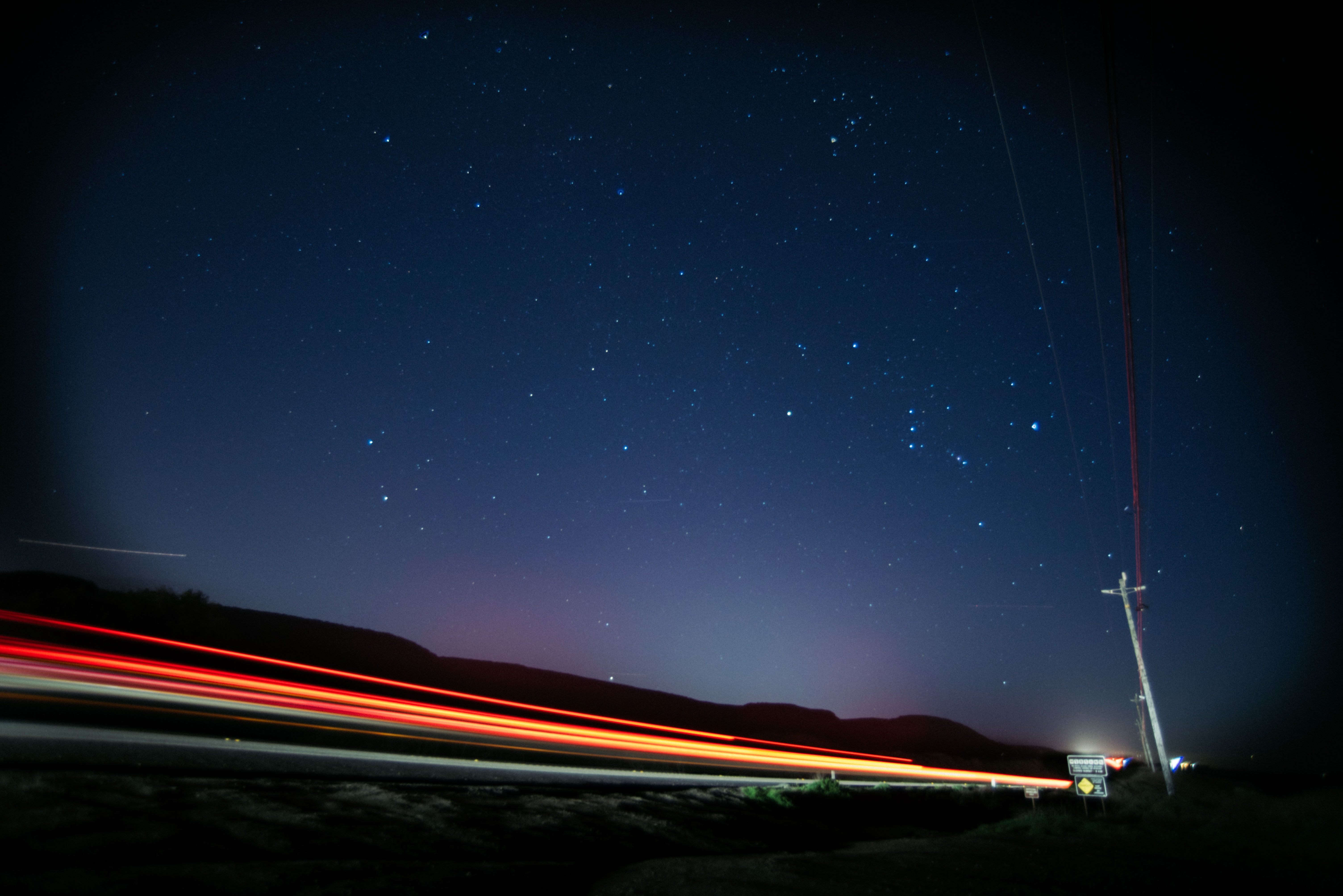 A slow shutter image depicting traffic in motion under a starlit sky on California State Route 1