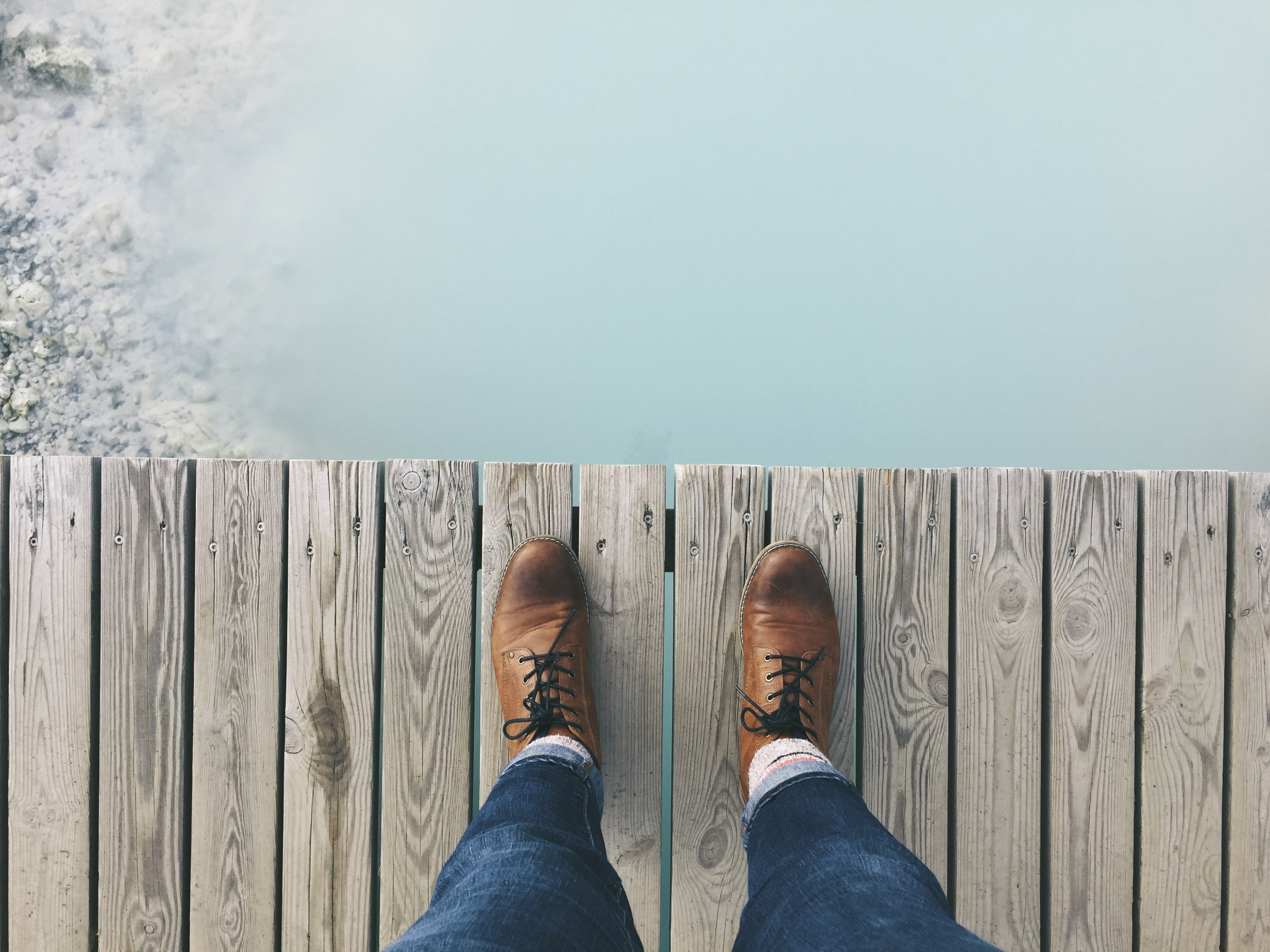 A person standing on a dock looking down on their brown shoes next to the water.