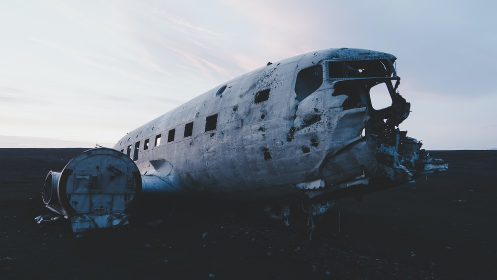 abandoned airplane on the floor under white clouds