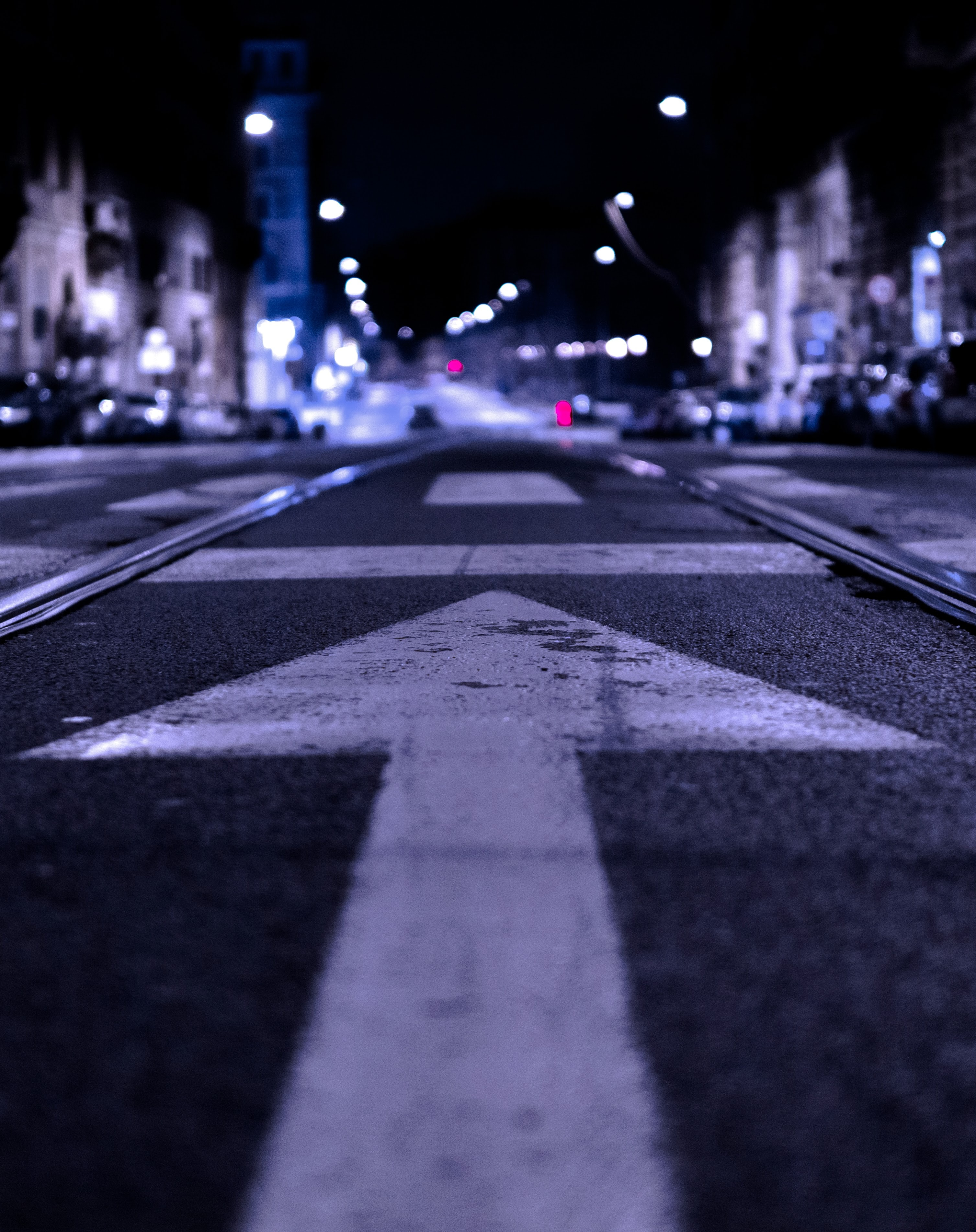A white arrow painted on an asphalt road in Rome in the evening