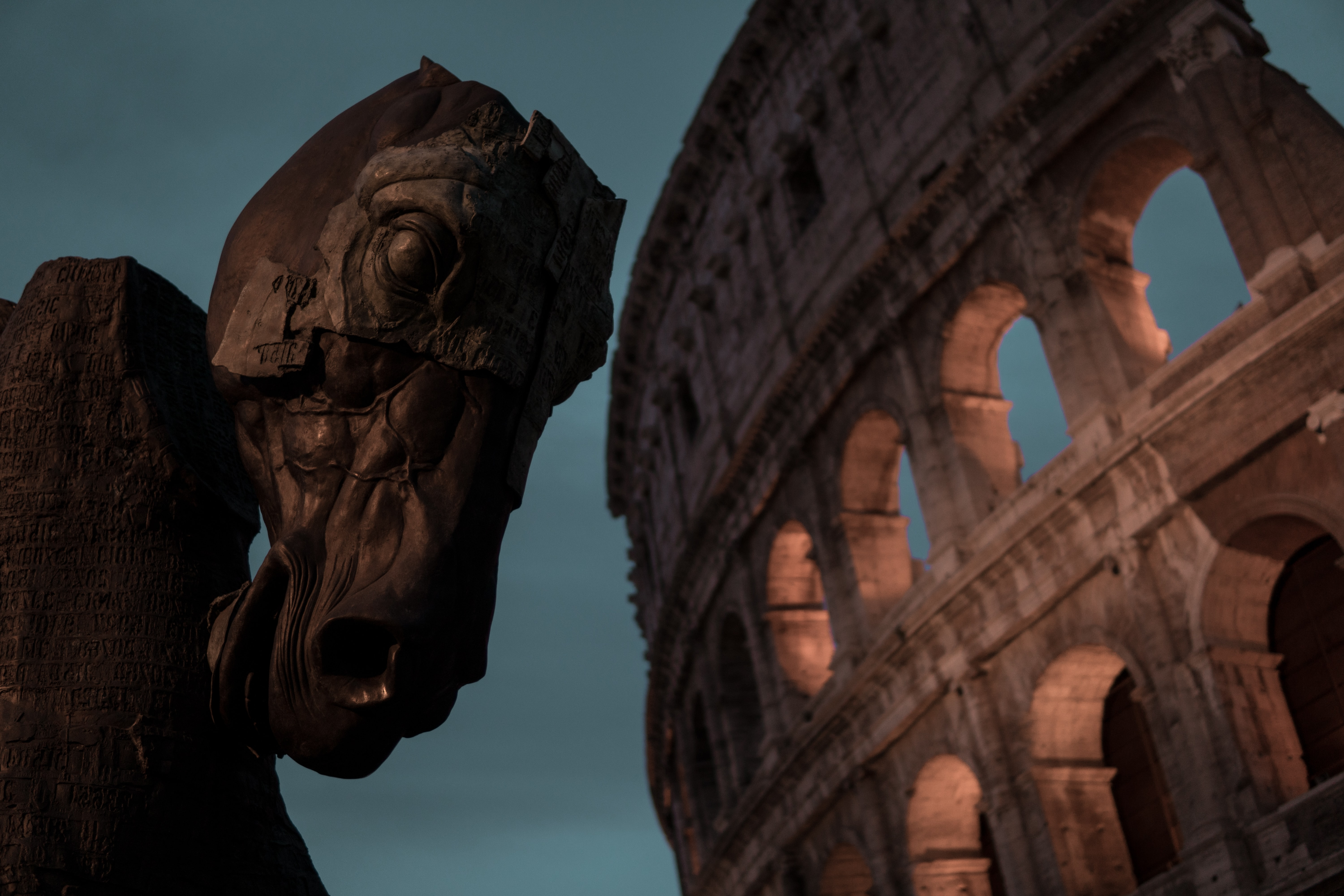 A horse head sculpture next to the Colosseum at dusk