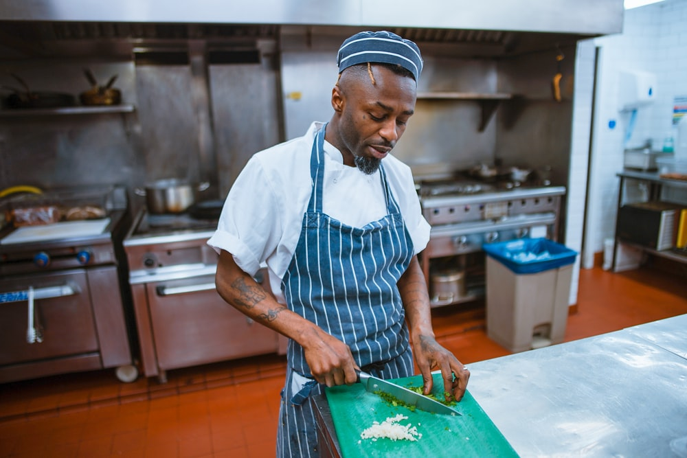 man chopping garlic gloves