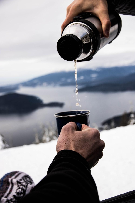 person pouring water in black ceramic mug