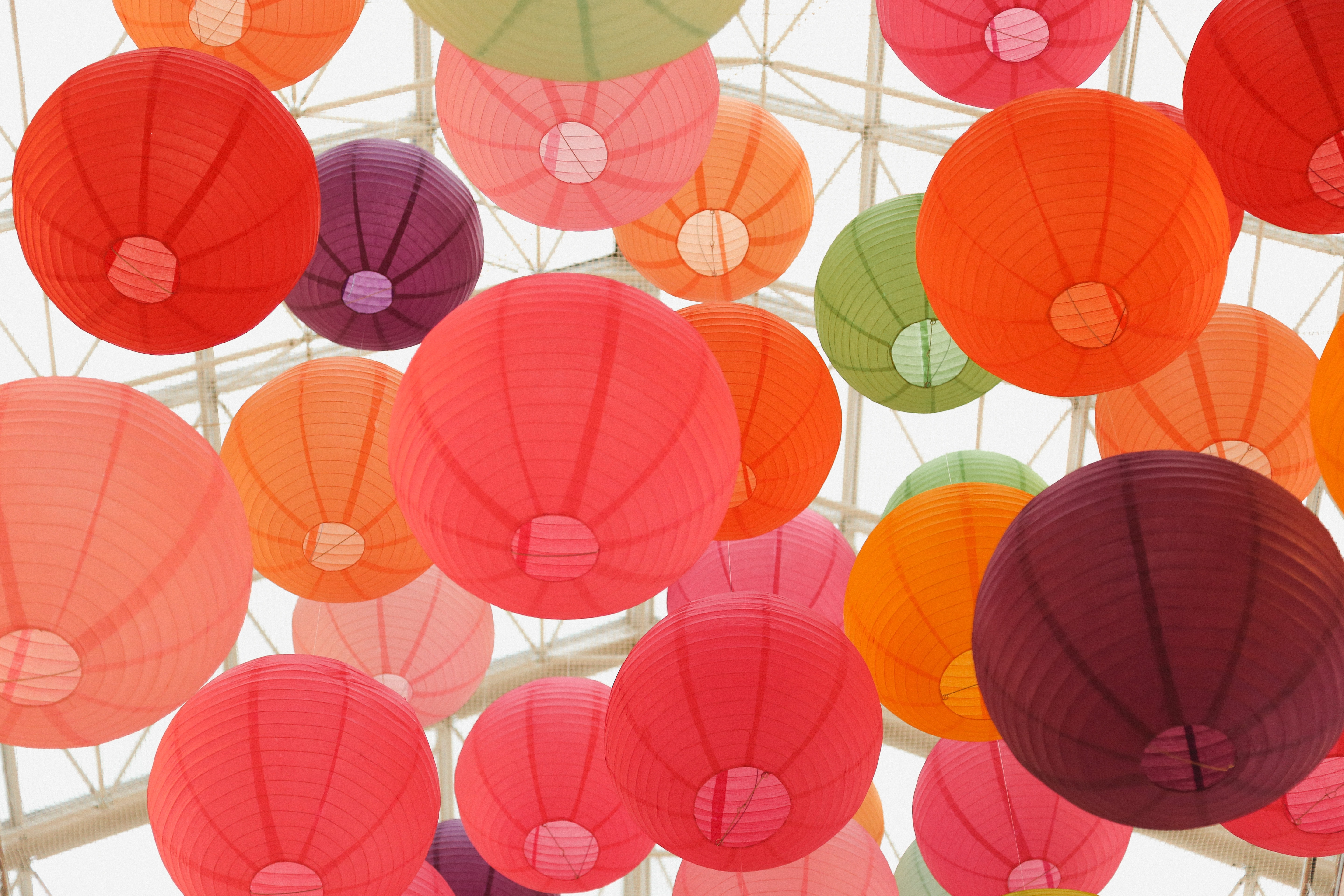 Large round colorful balloons floating to the roof of a glass house.