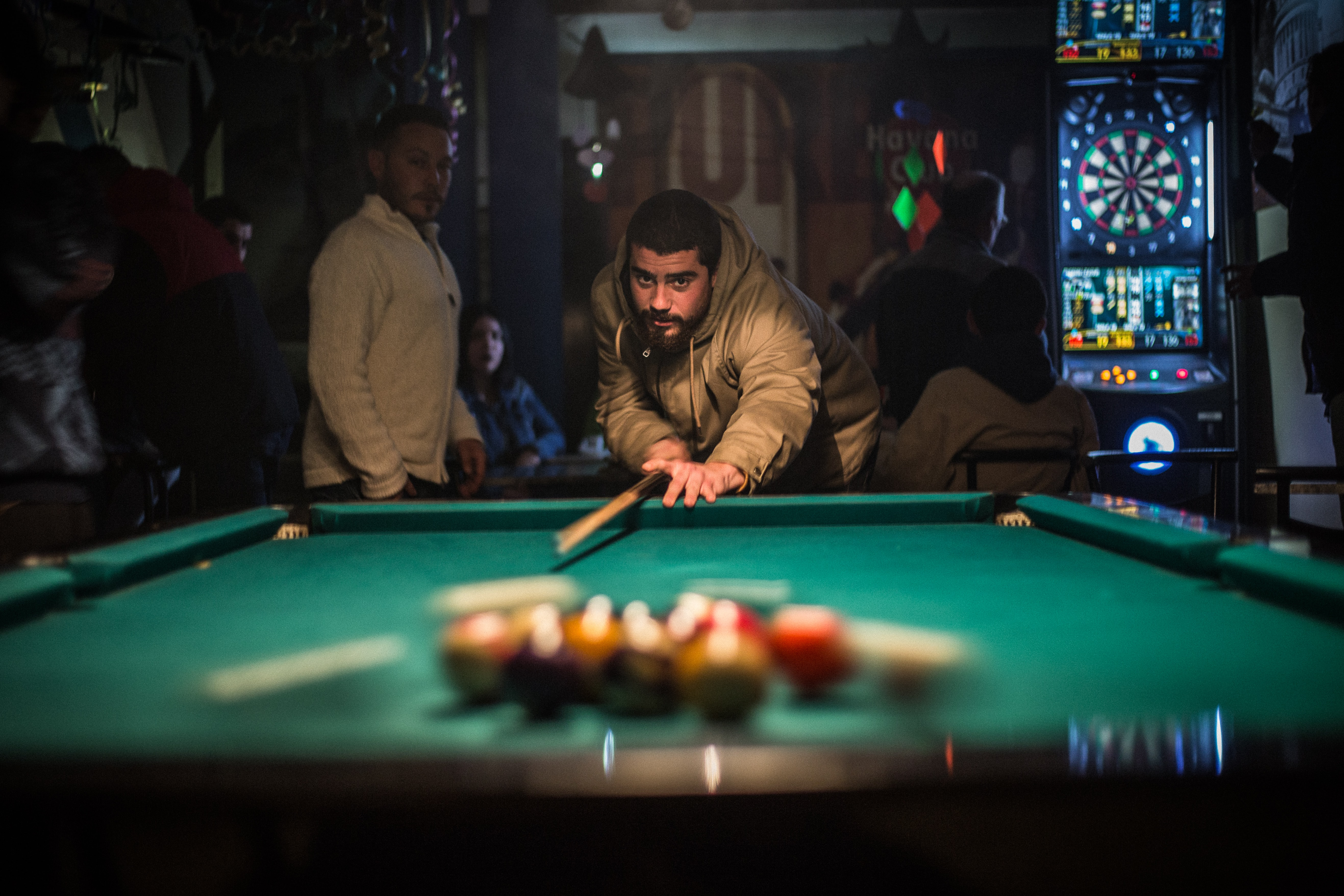 A man playing snooker on a pool table with his friend by his side in a bar in Cuba
