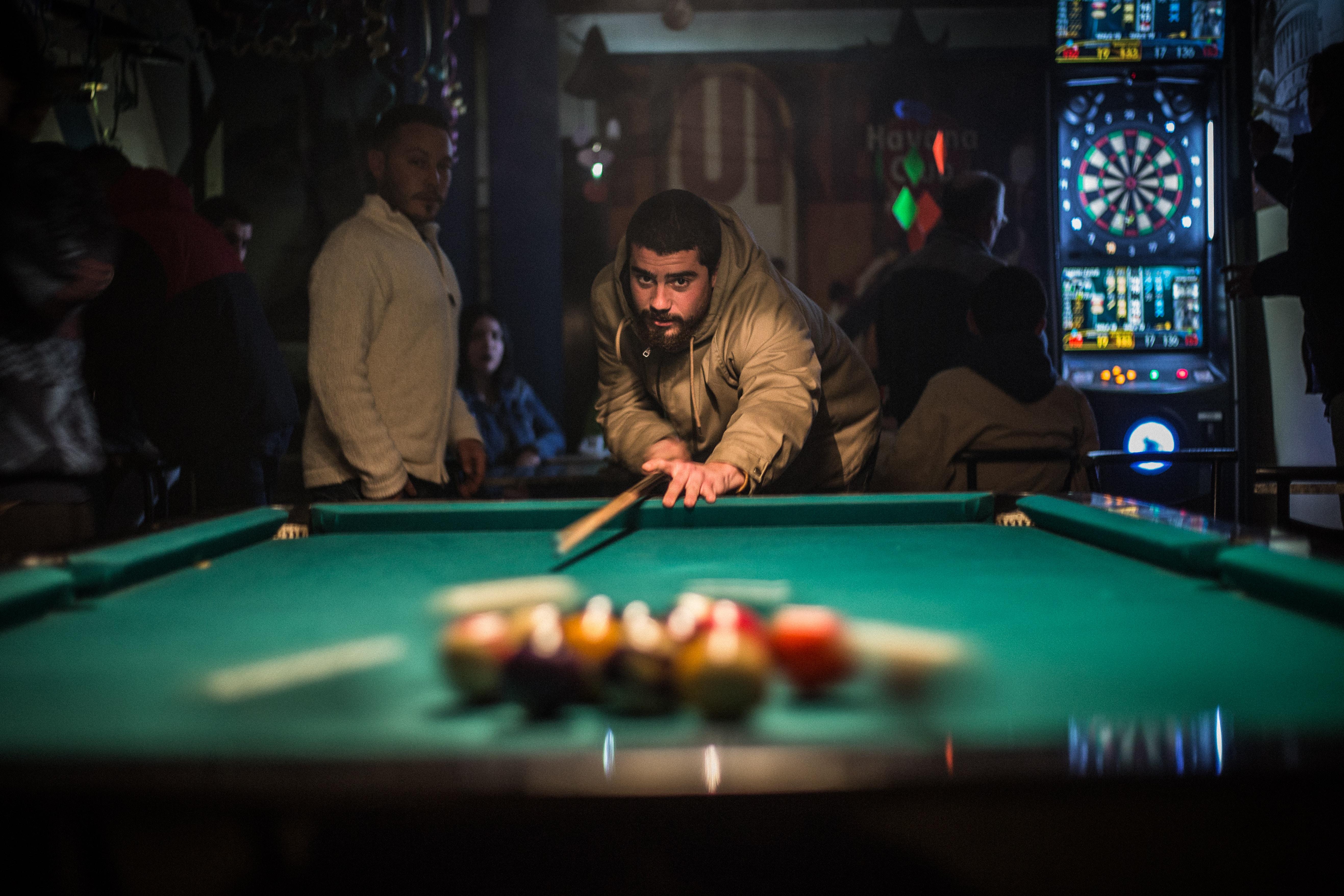 man in brown jacket playing billiard