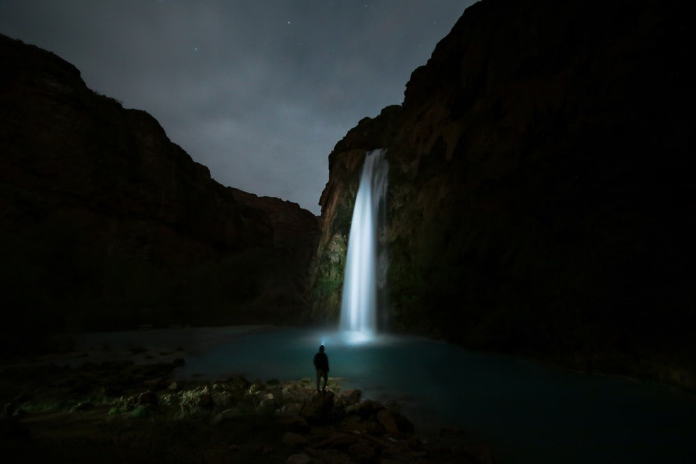 person standing on the ground staring the waterfalls