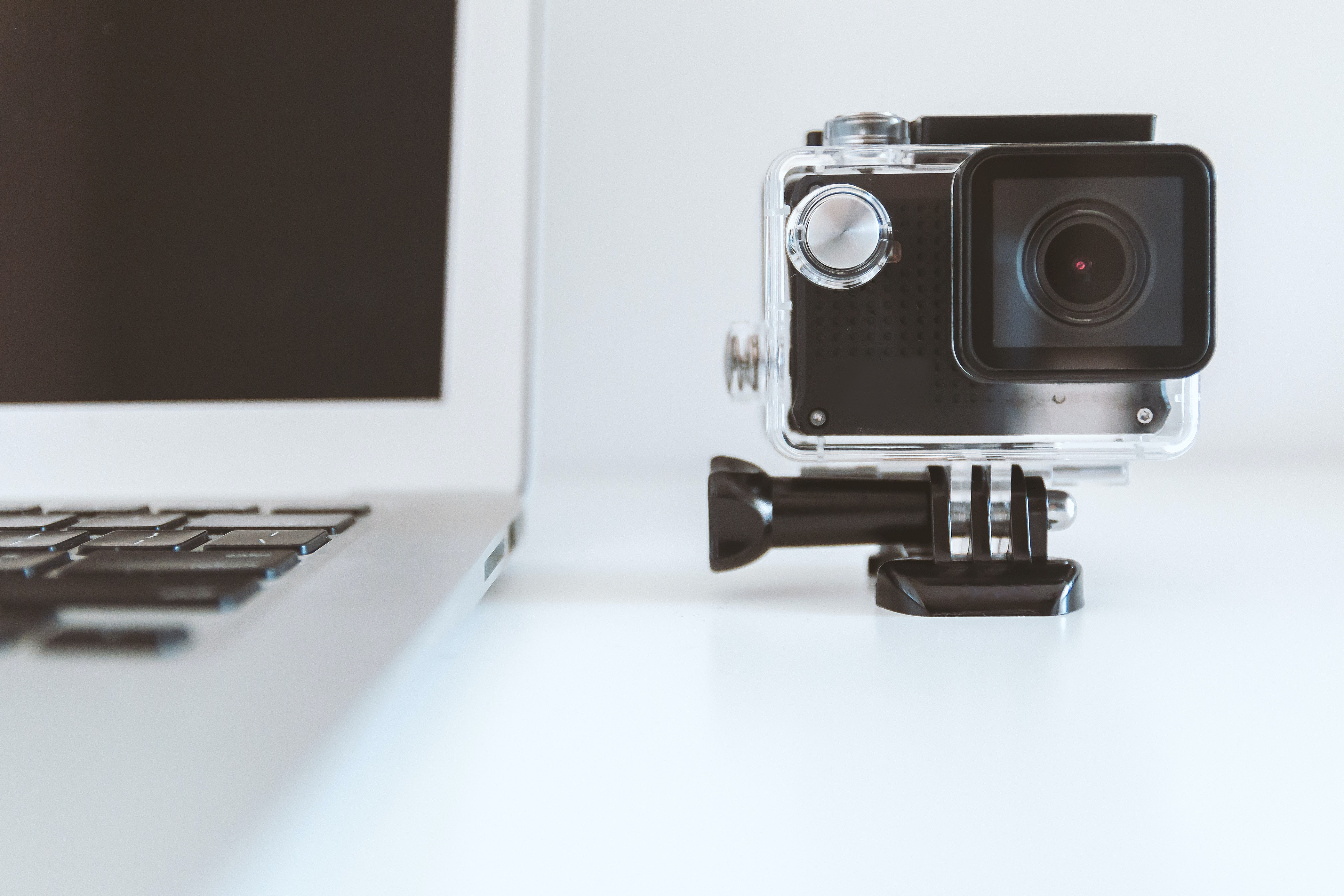 black action camera beside white laptop