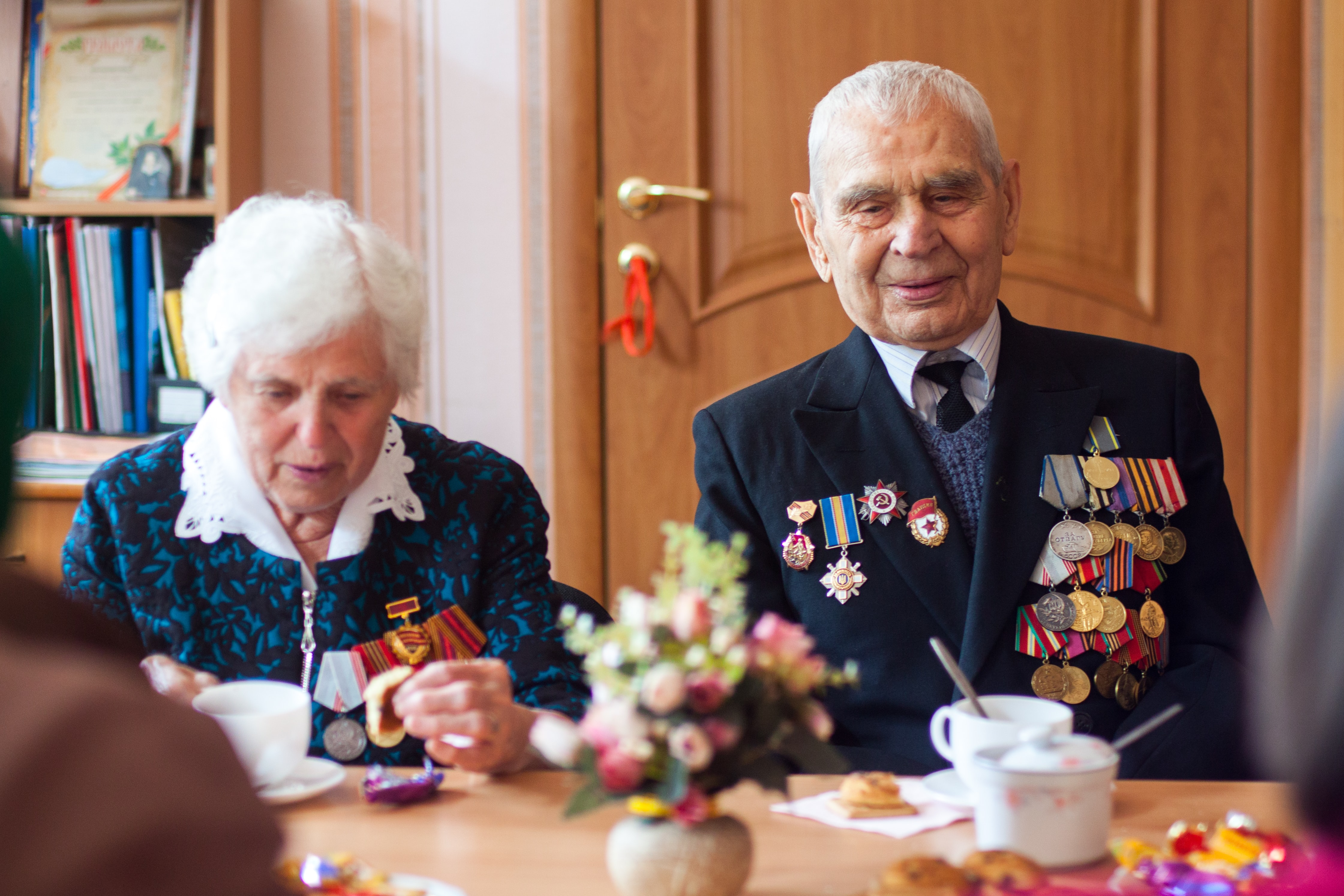 A retired and old Ukraine soldier sitting with his wife and medals on his jacket.