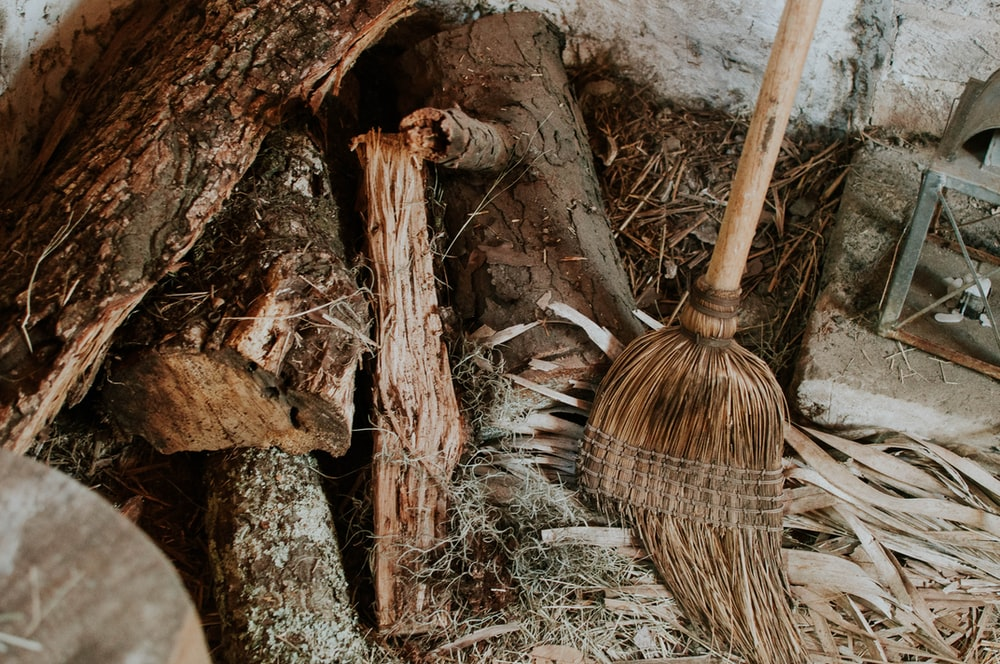 A broom leaning against a wall next to a disorderly heap of firewood