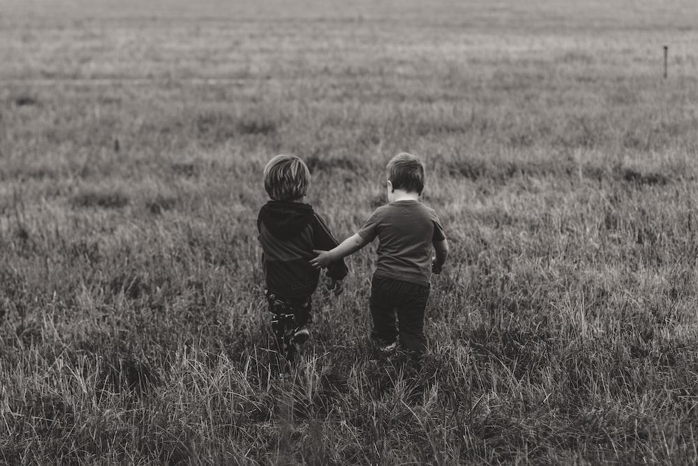 two boy's walking on green grass field