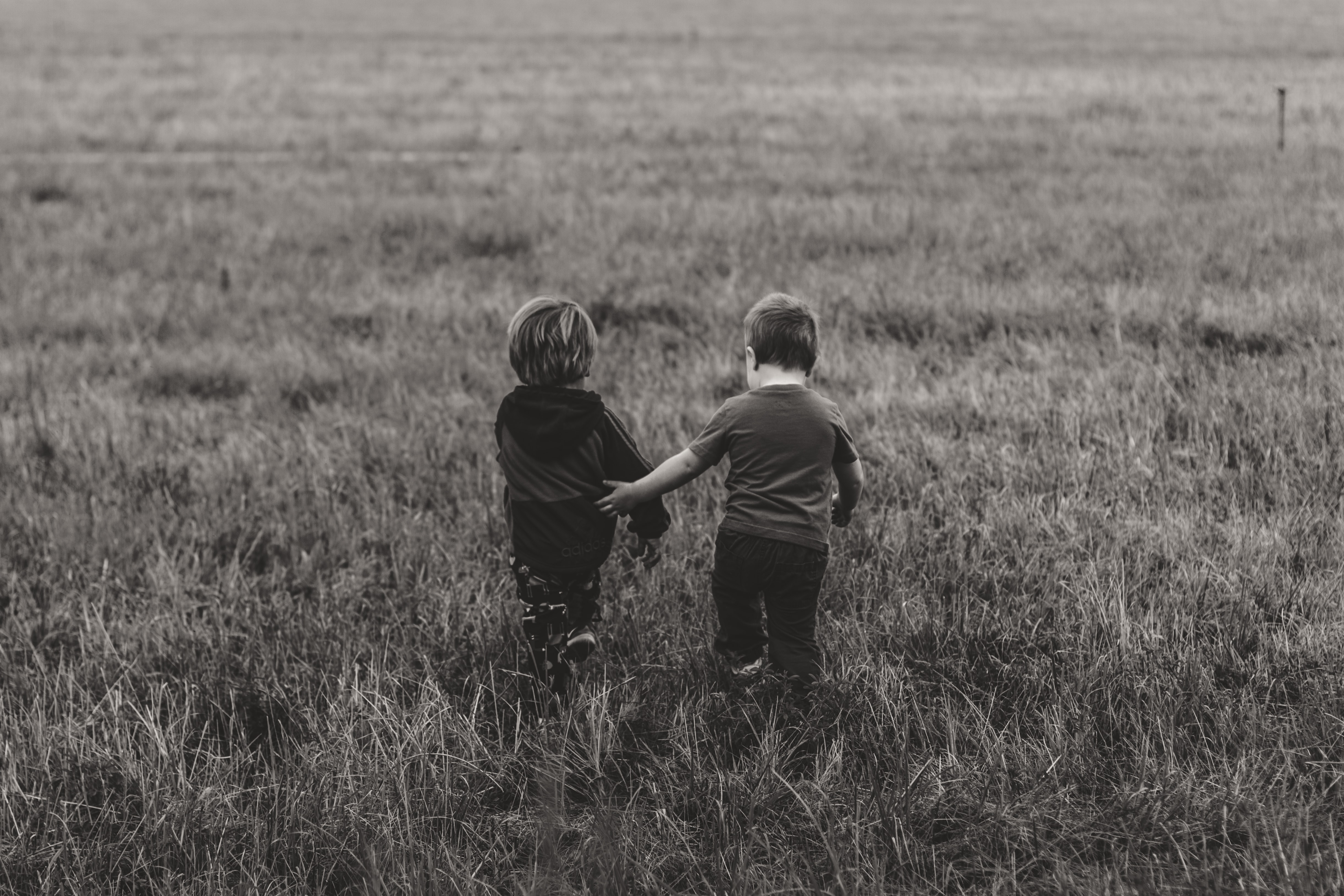 Two children walk arm in arm away from camera in black and white photo