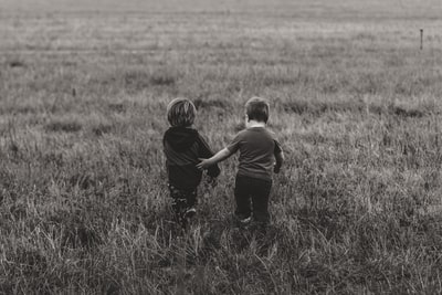 two boy's walking on green grass field friend teams background