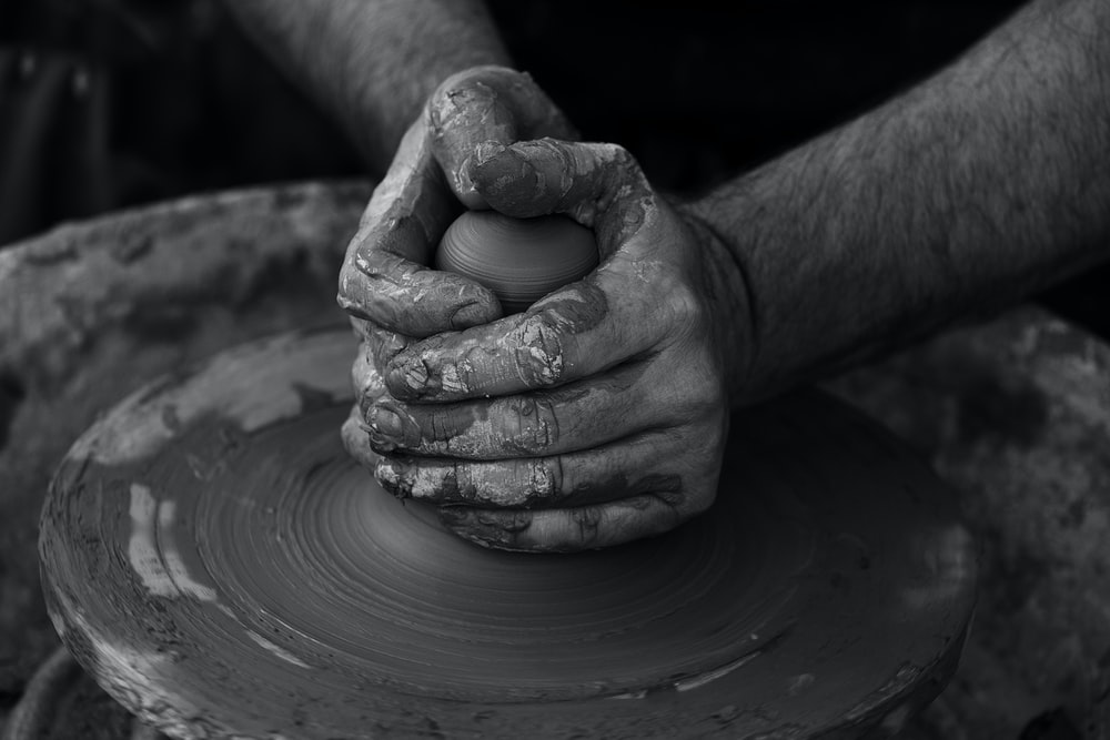 grayscale photography of person's hand making pot