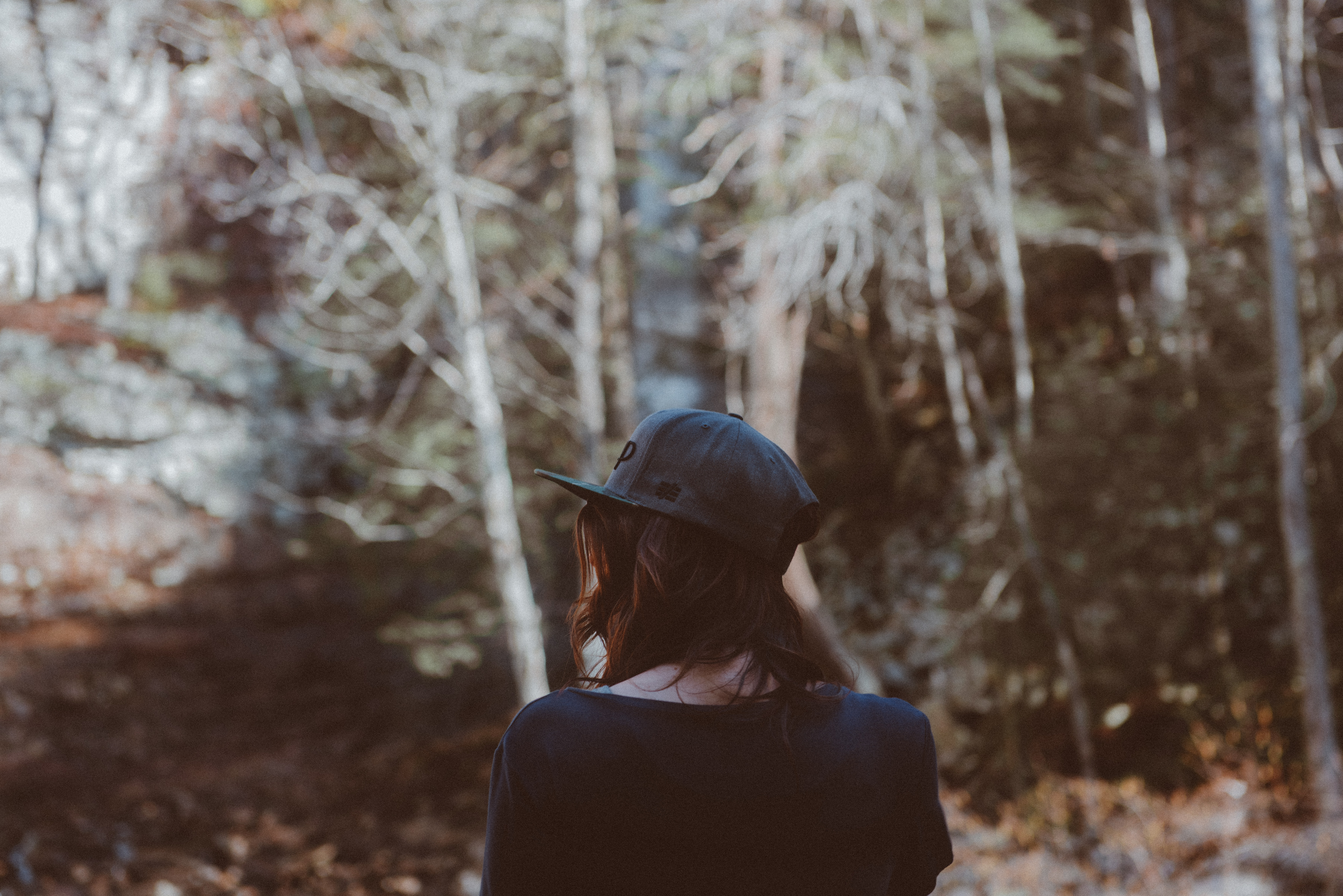 The back of a girl wearing a baseball cap standing in a forest