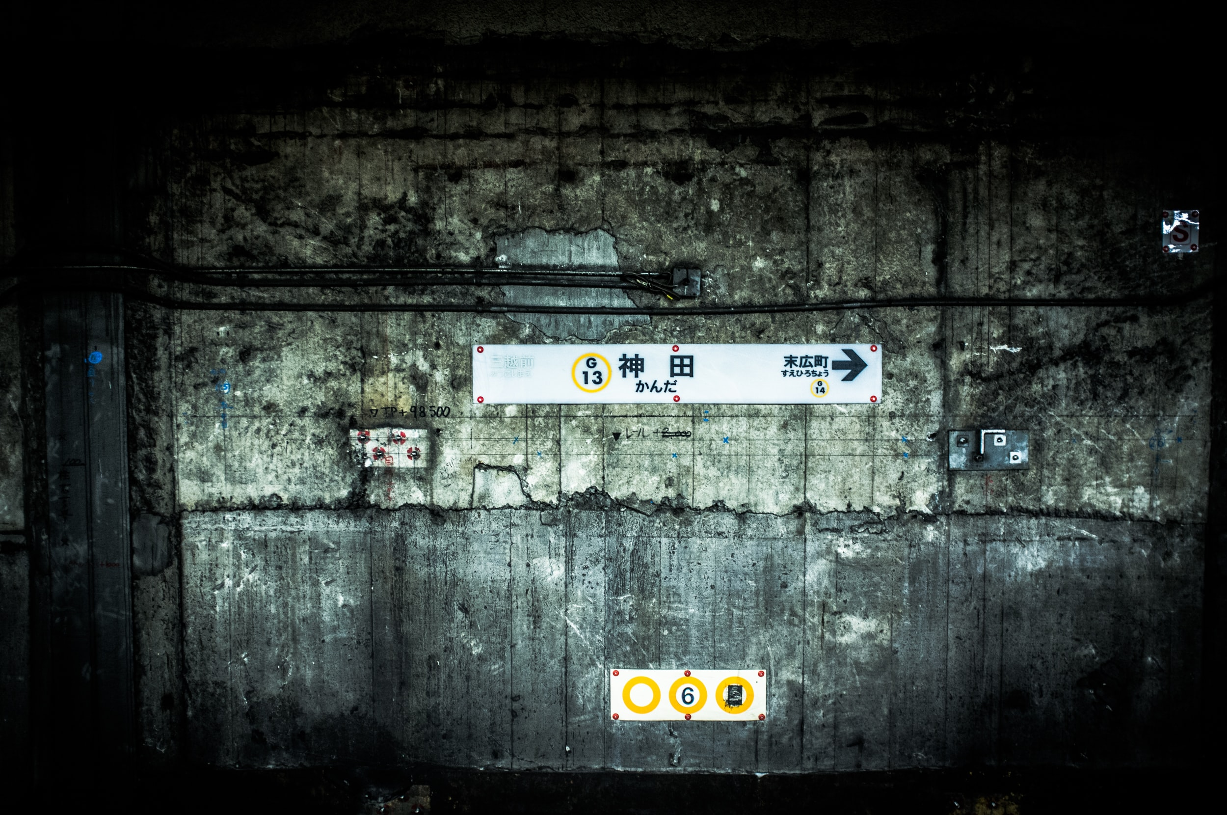 White signs showing the direction on a worn-out wall at a railway station