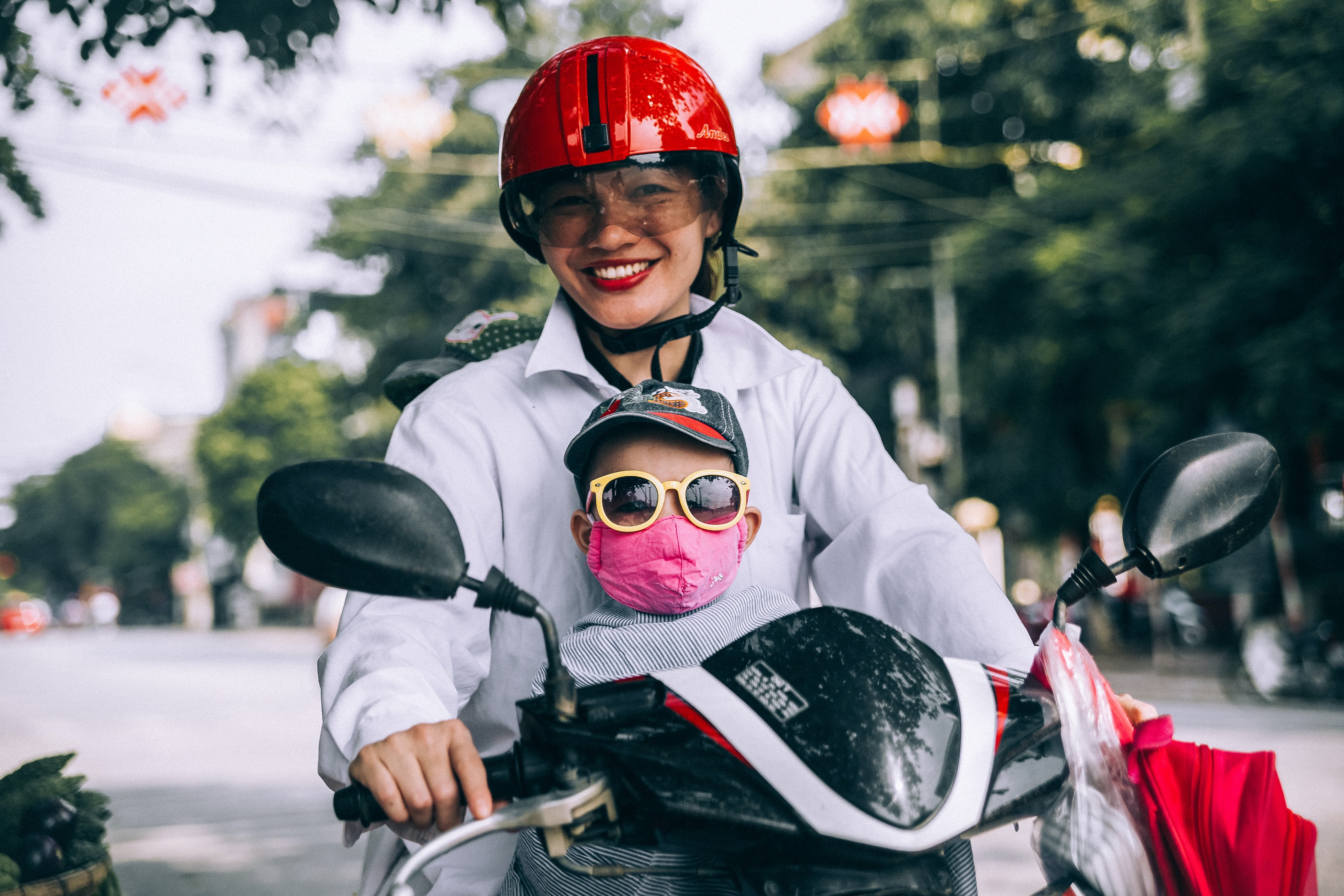 Riding a scooter together, mother wears a hat and child wears sunglasses, face mask and cap