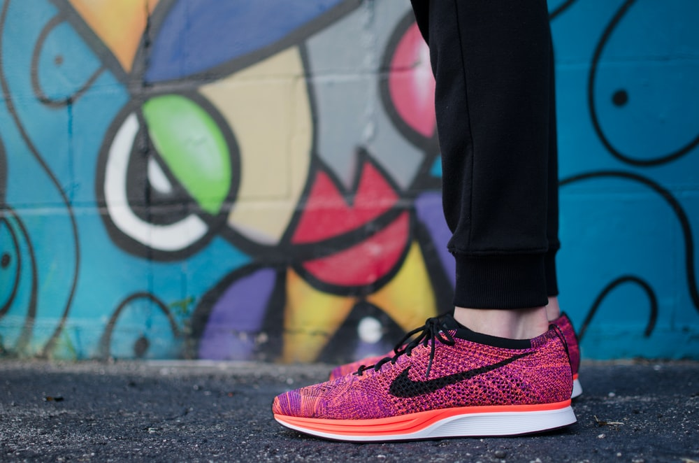 person showing pair of pink Nike low-top sneakers