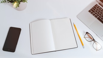 An open empty notebook on a white desk next to an iPhone and a MacBook