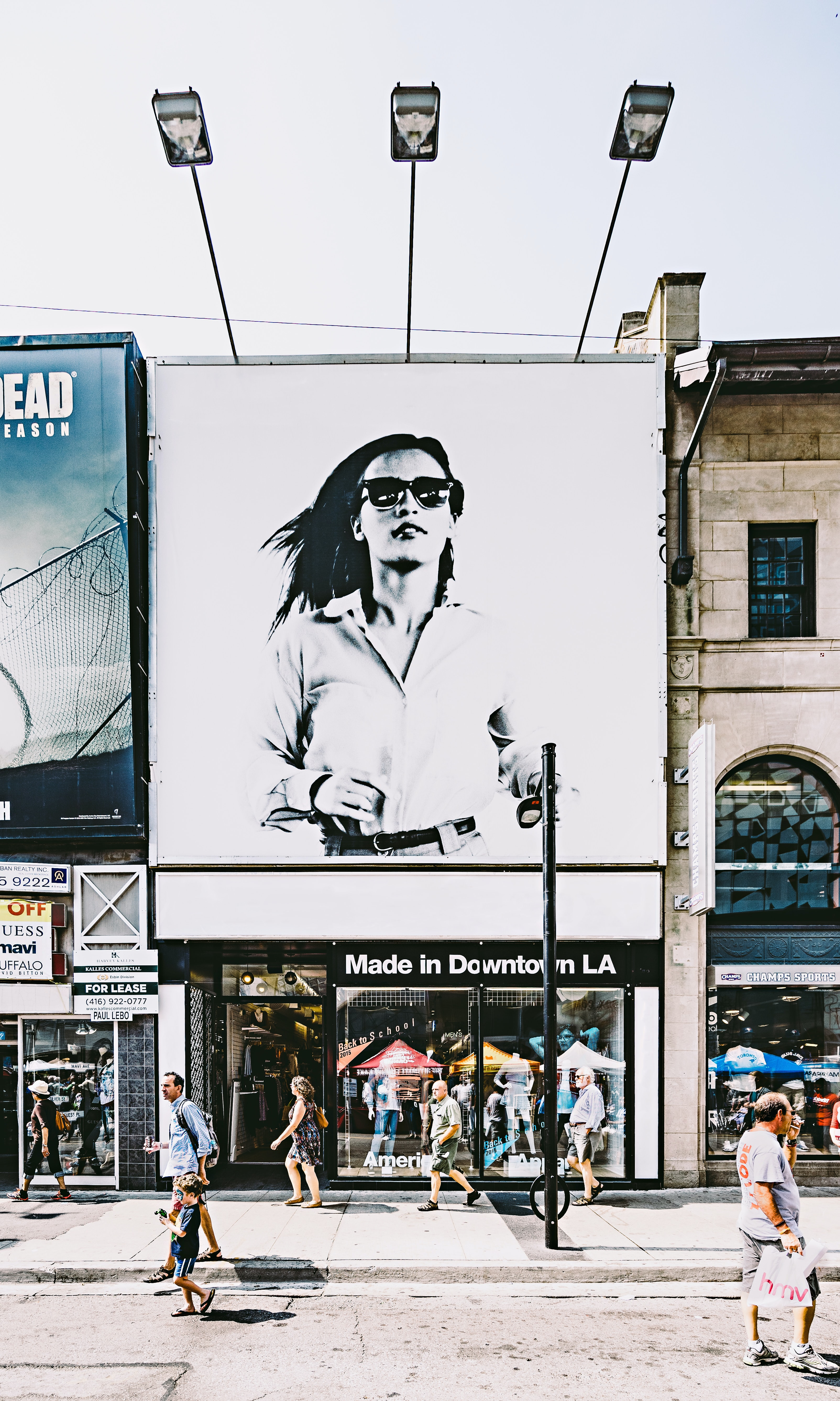 A large advertisement with an elegant woman in sunglasses over a storefront