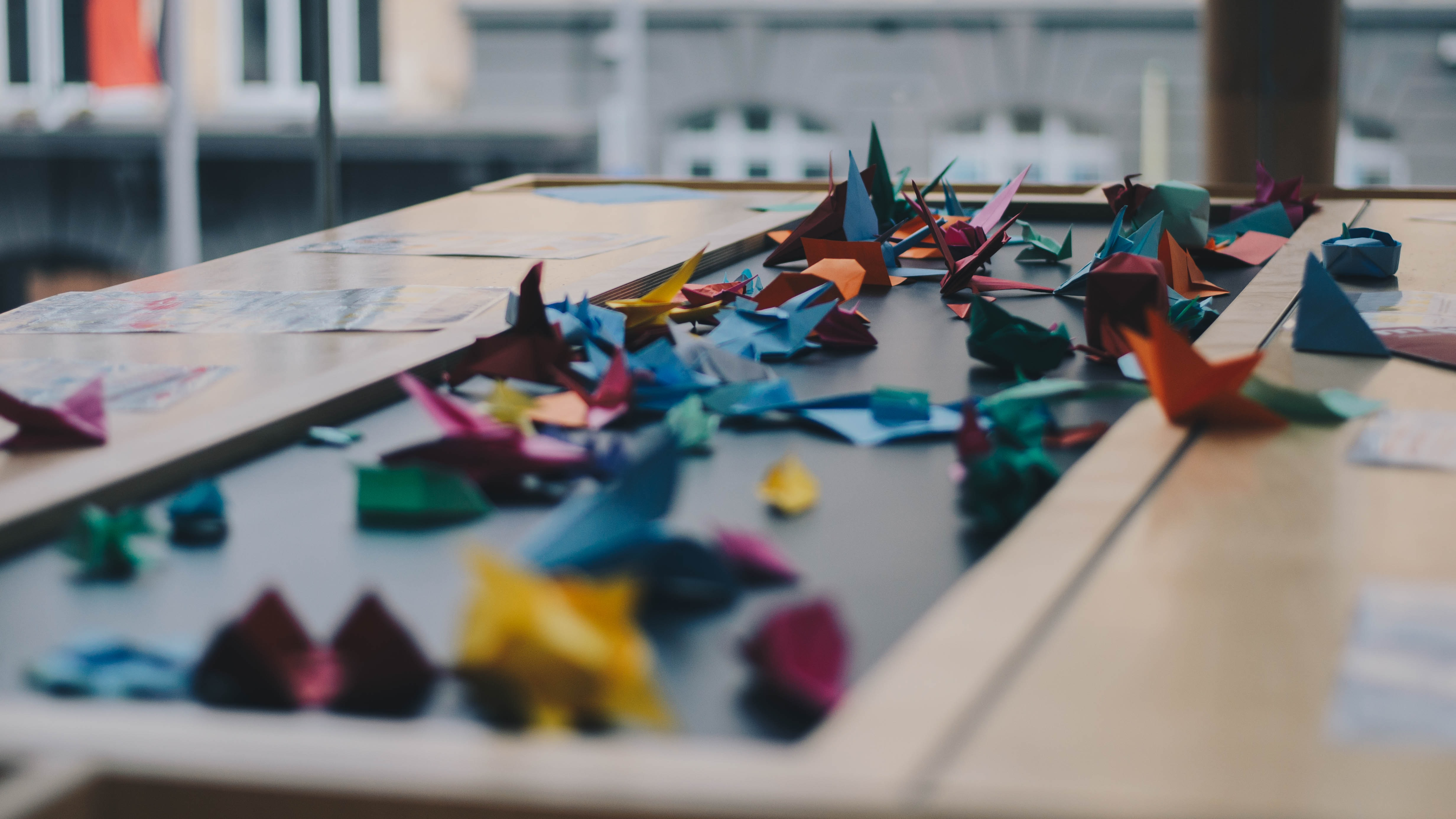 A large number of colorful origami cranes scattered across a table