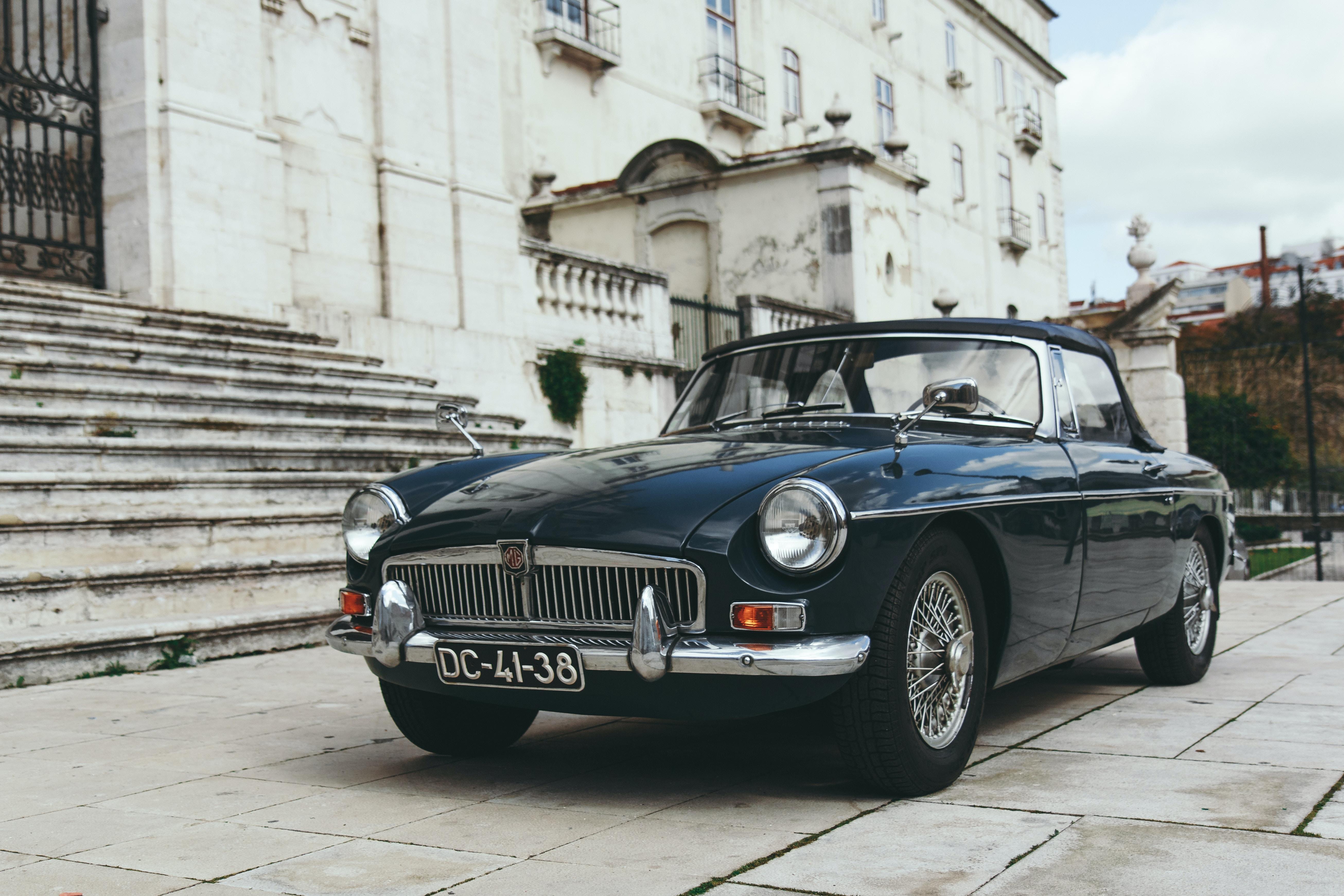 Vintage black car parked in front of a historic building in Lisbon.