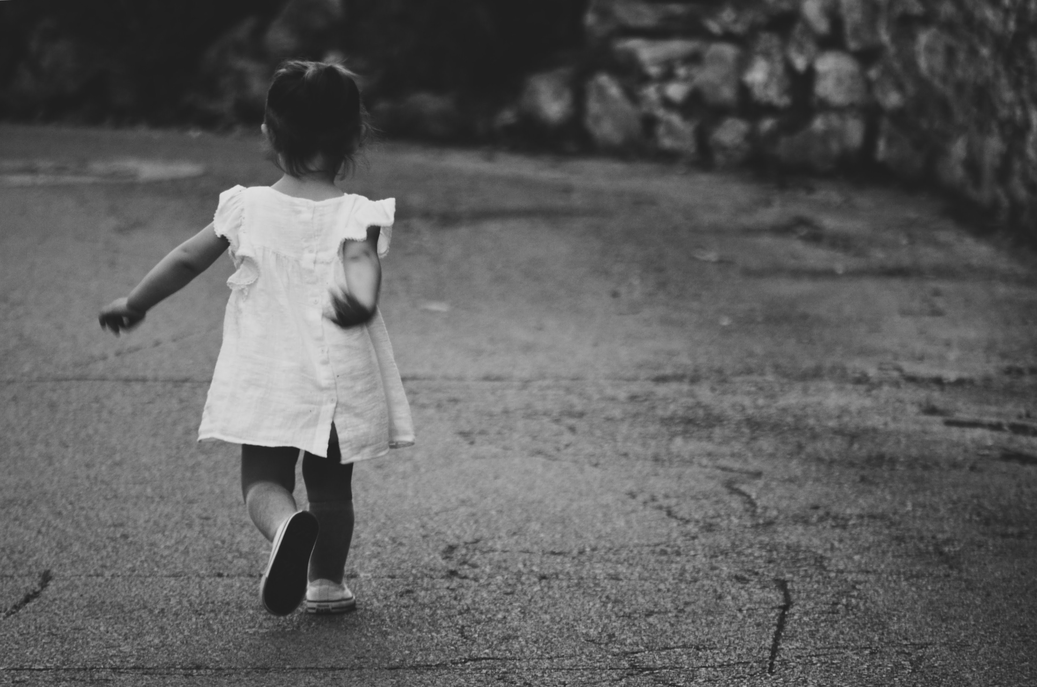 Black and white shot of lone young child running in white dress on pavement in Montpellier