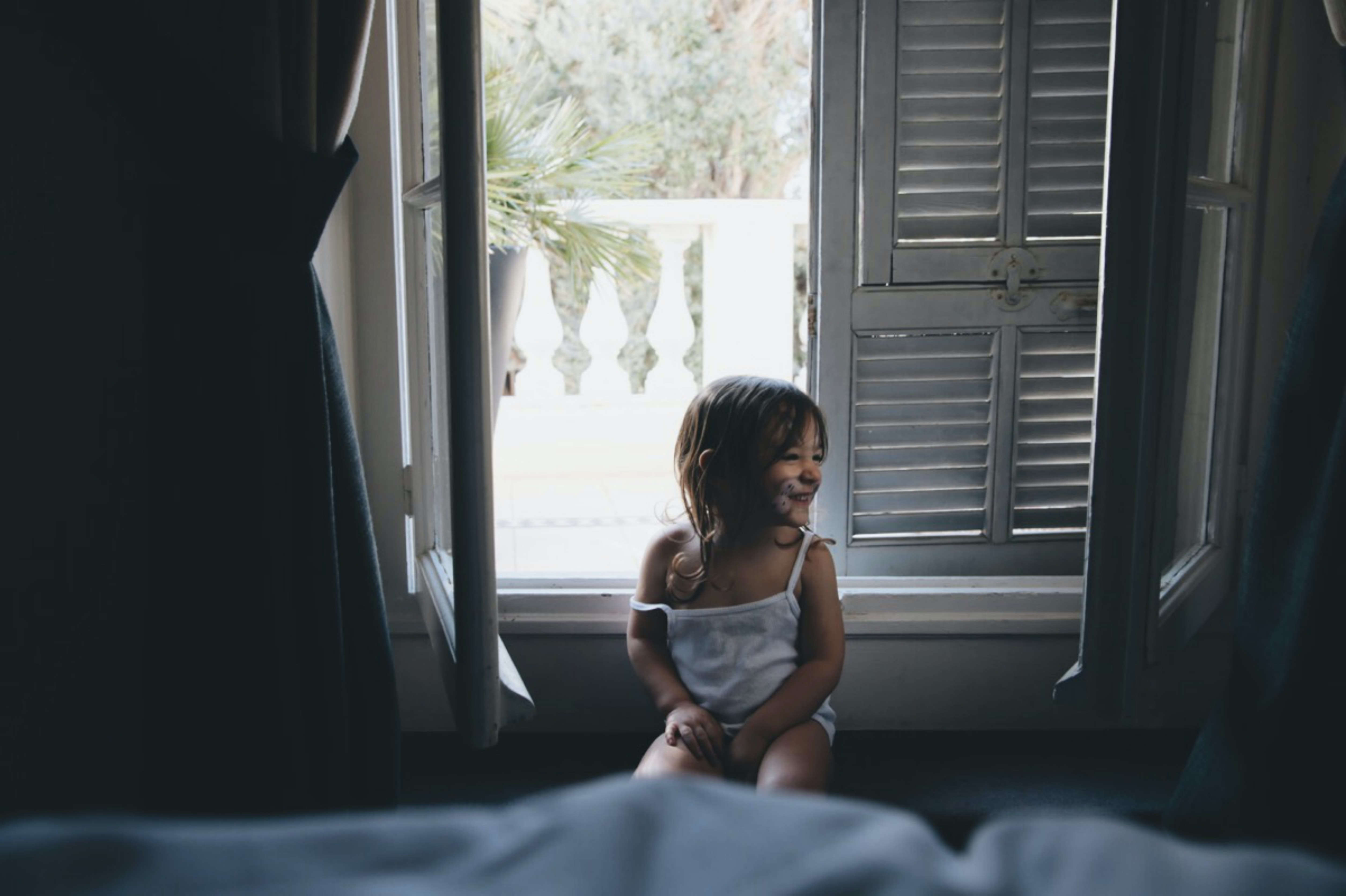 girl sitting by the window during daytime