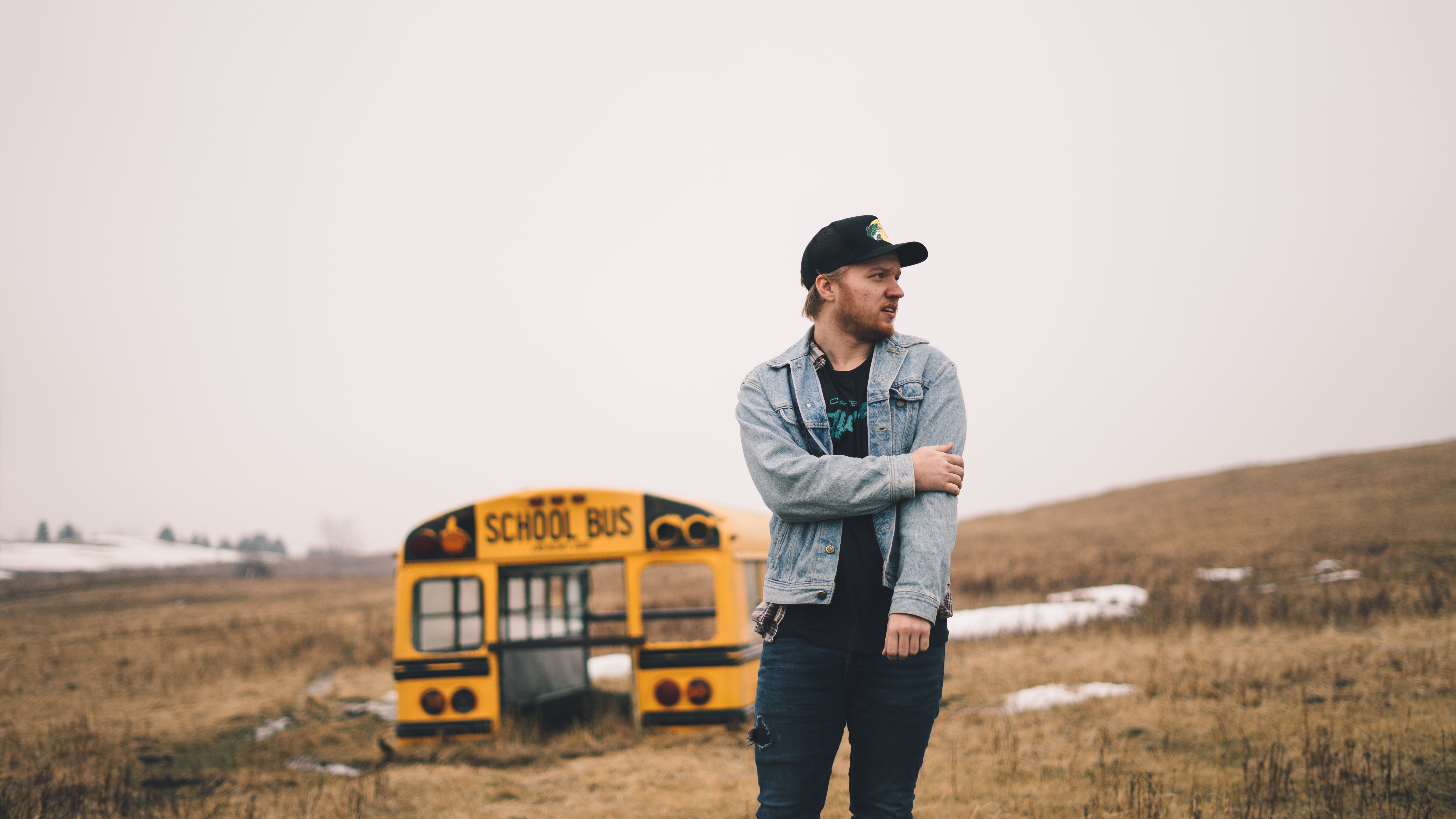 A man wearing a denim jacket holding his arm while staring down the street, standing in front of a crashed school bus in a country field