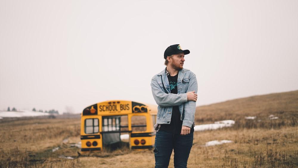 man standing on grass field near school bus part during daytime