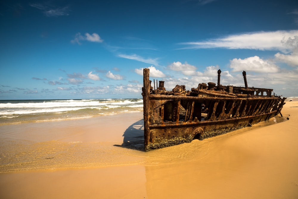 brown shipwreck on coast during daytime
