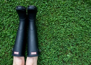 person wearing pair of black rain boots