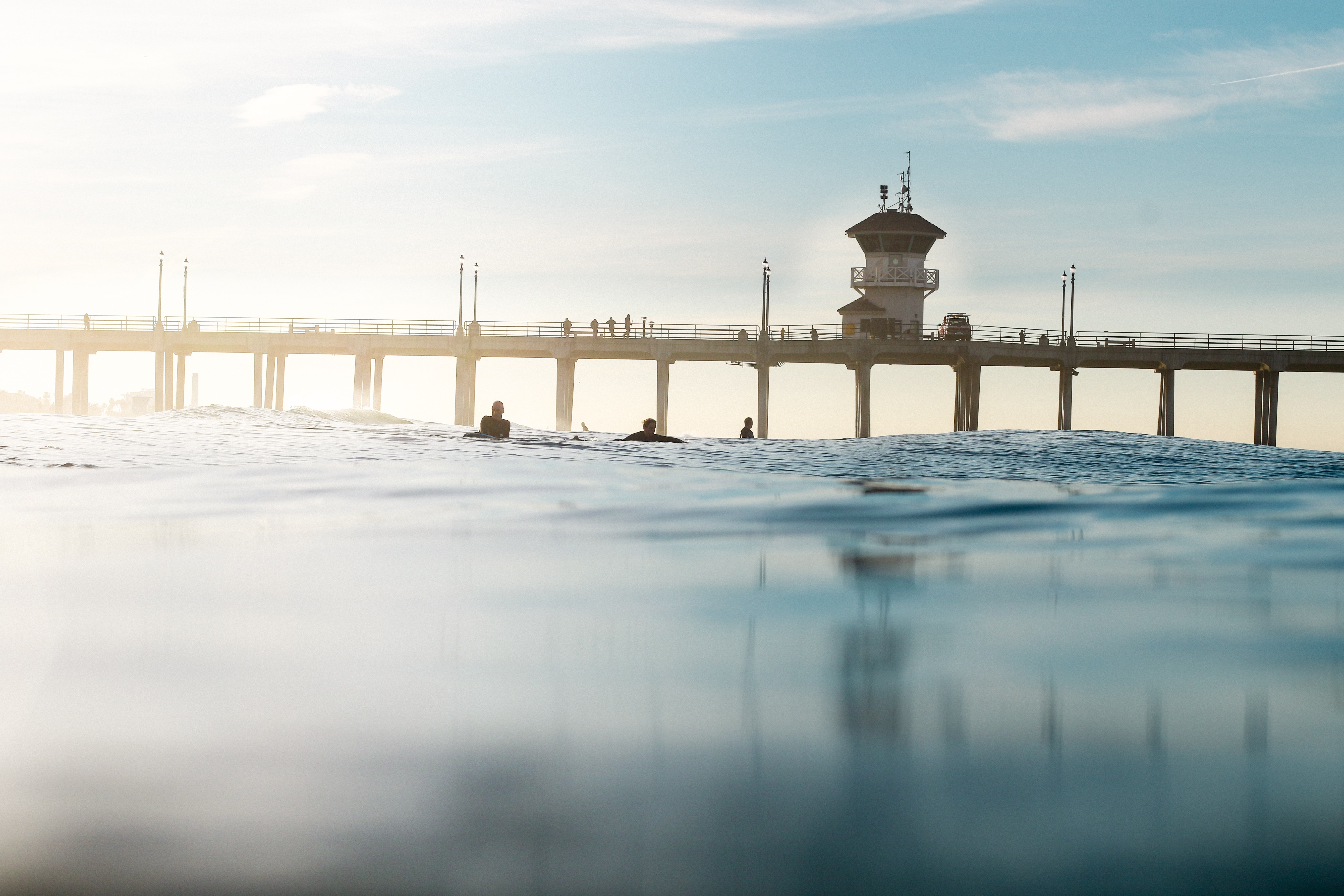 Pier and surfers from the water surface at Huntington Beach